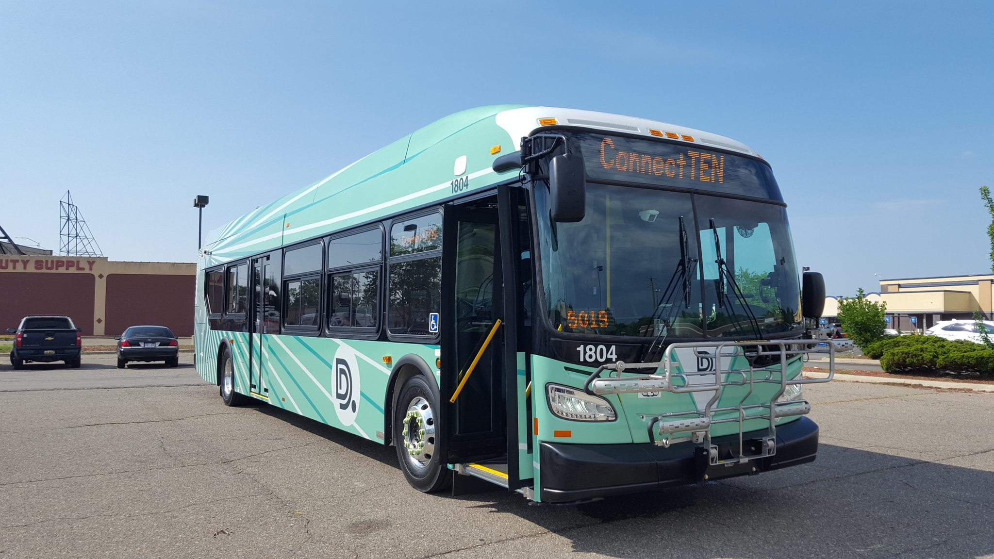 "A light green bus with painted green and white rays emanating from the upper back corner. On the screen above the front window it reads, ""Connect Ten."""