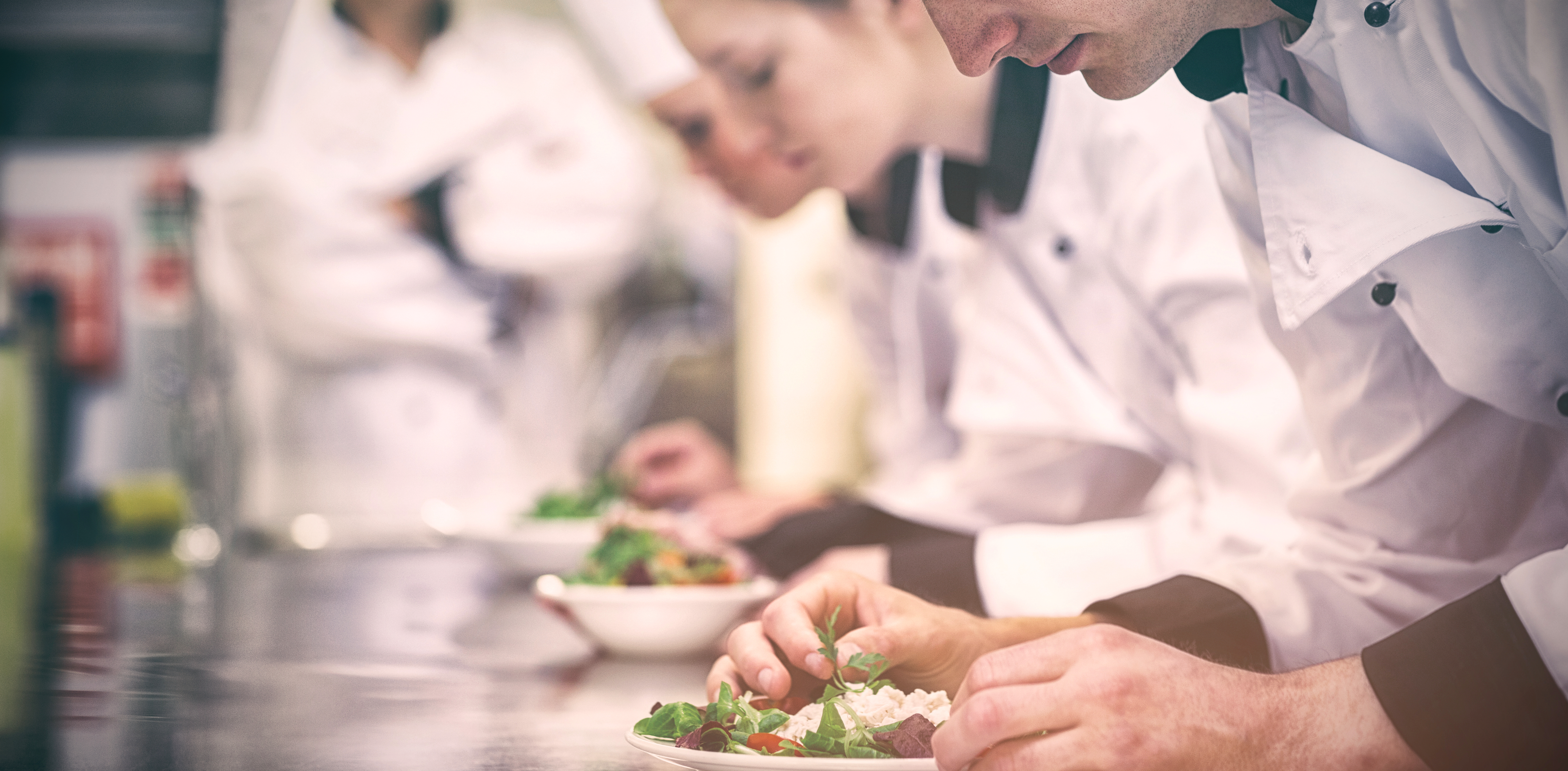Culinary students plate a dish
