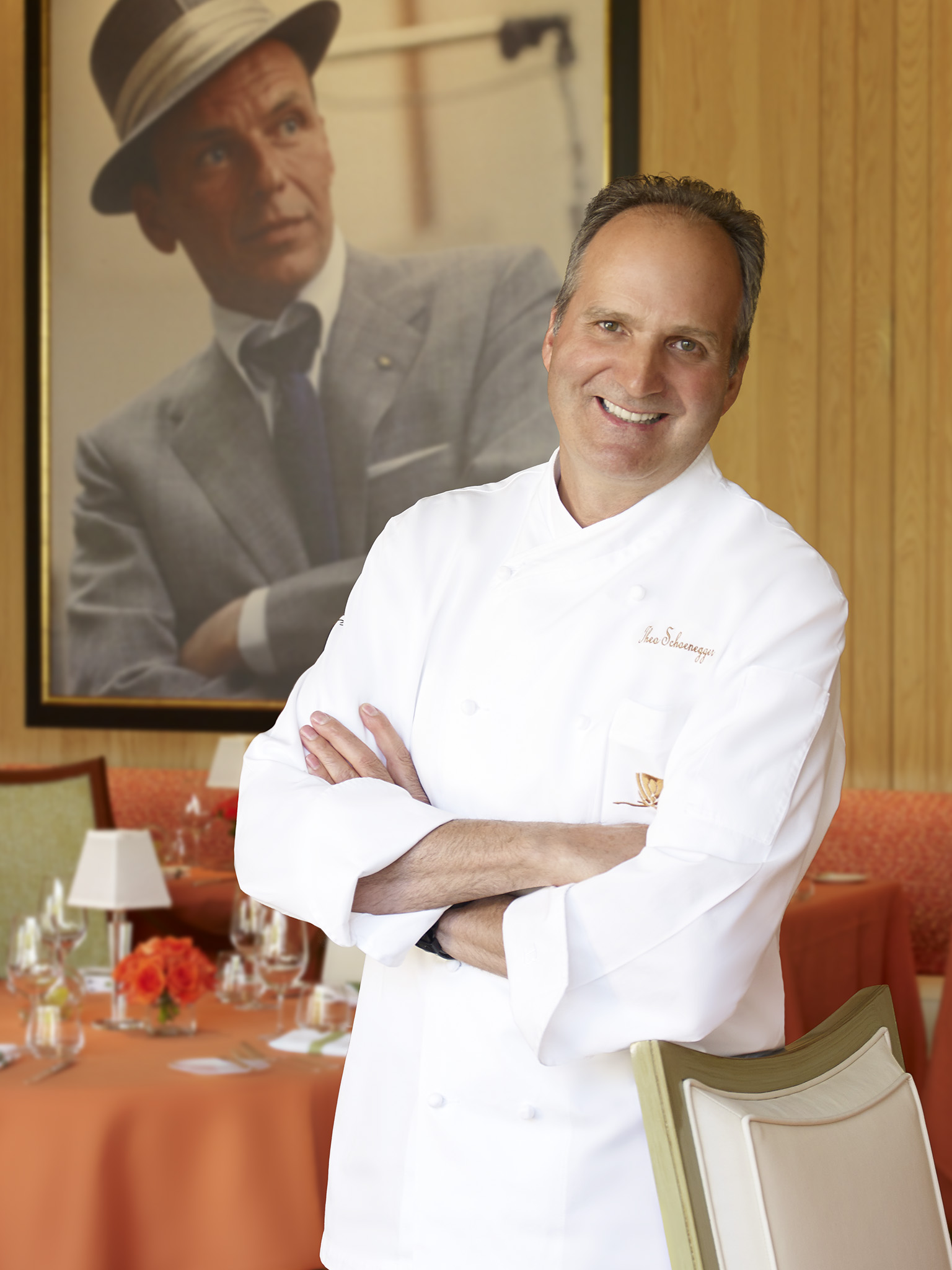 A chef in a white coat with his arms crossed standing in front of a photo of Frank Sinatra