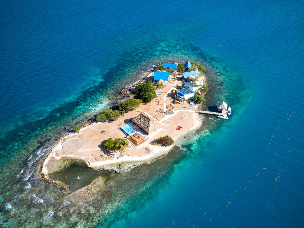 Aerial view of a private island surrounded by turquoise waters. A few buildings sit on one side of the island, where there's also a dock.