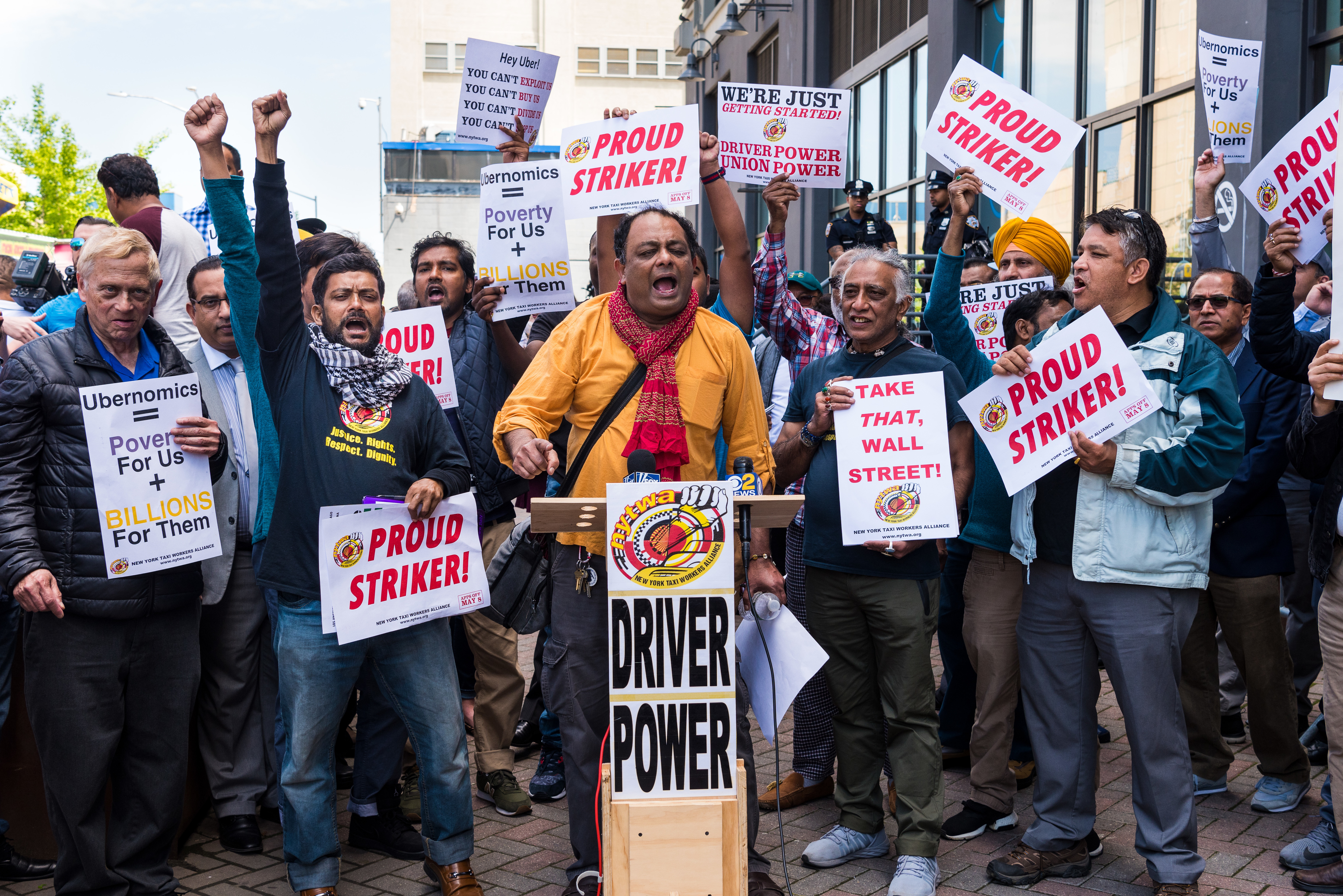 "Cab drivers carrying signs that read ""Driver power"" and "" Proud striker"" raise their fists in the air and yell outside Uber and Lyft offices in New York."