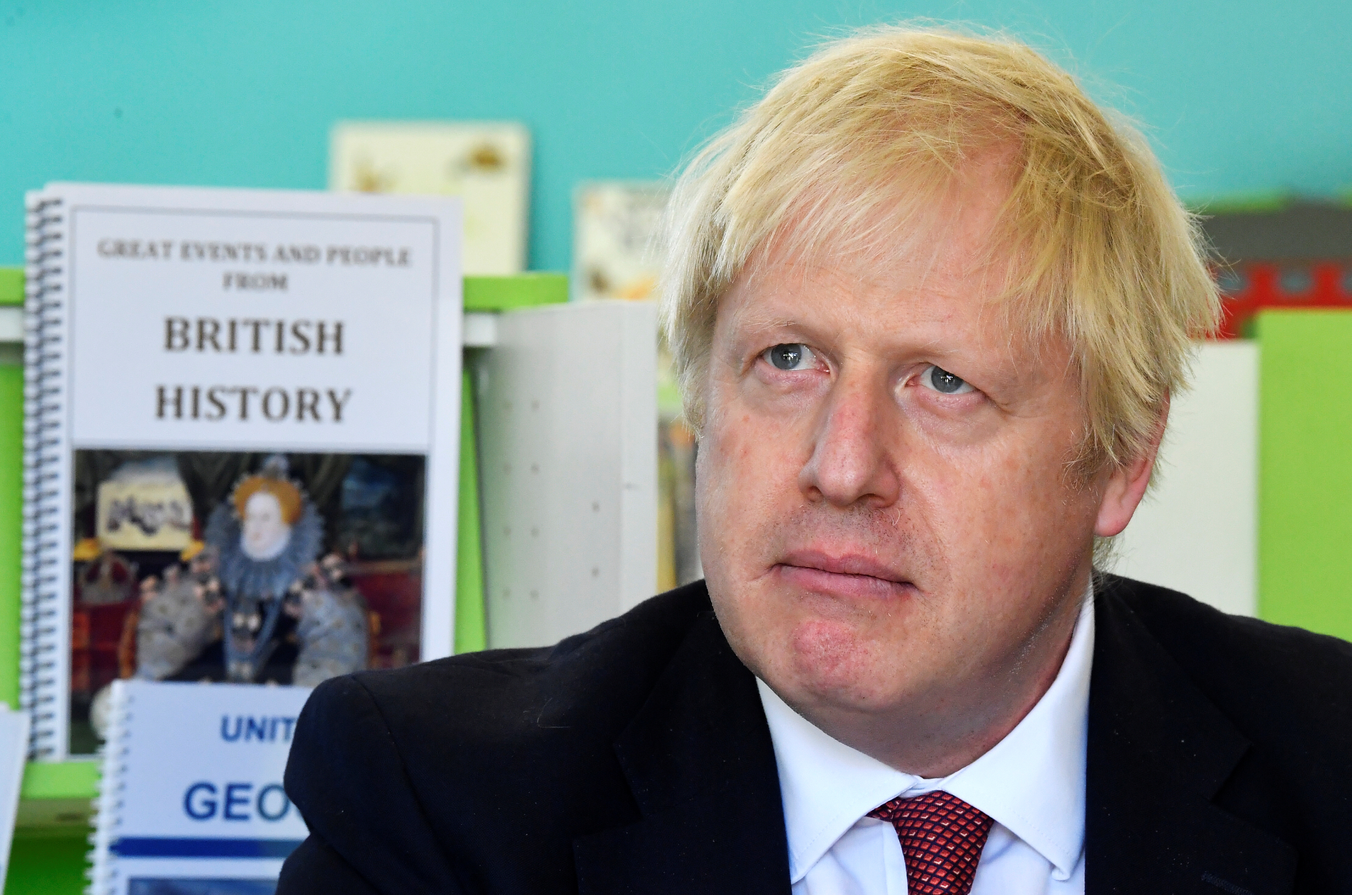British Prime Minister Boris Johnson in a classroom with a British history textbook on a shelf behind him.