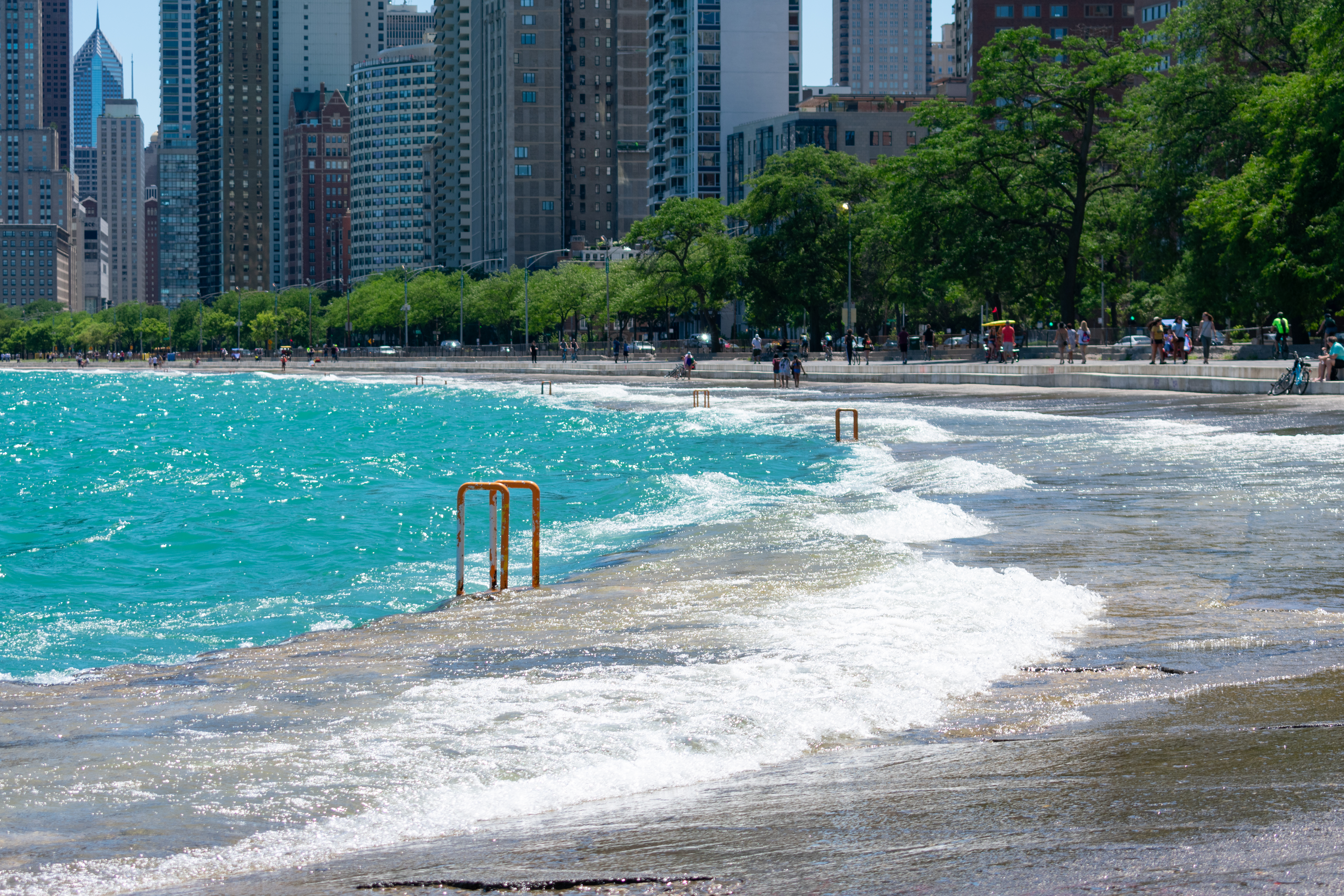 Waves crashing onto a path next to a multilane road and a row of tall buildings.