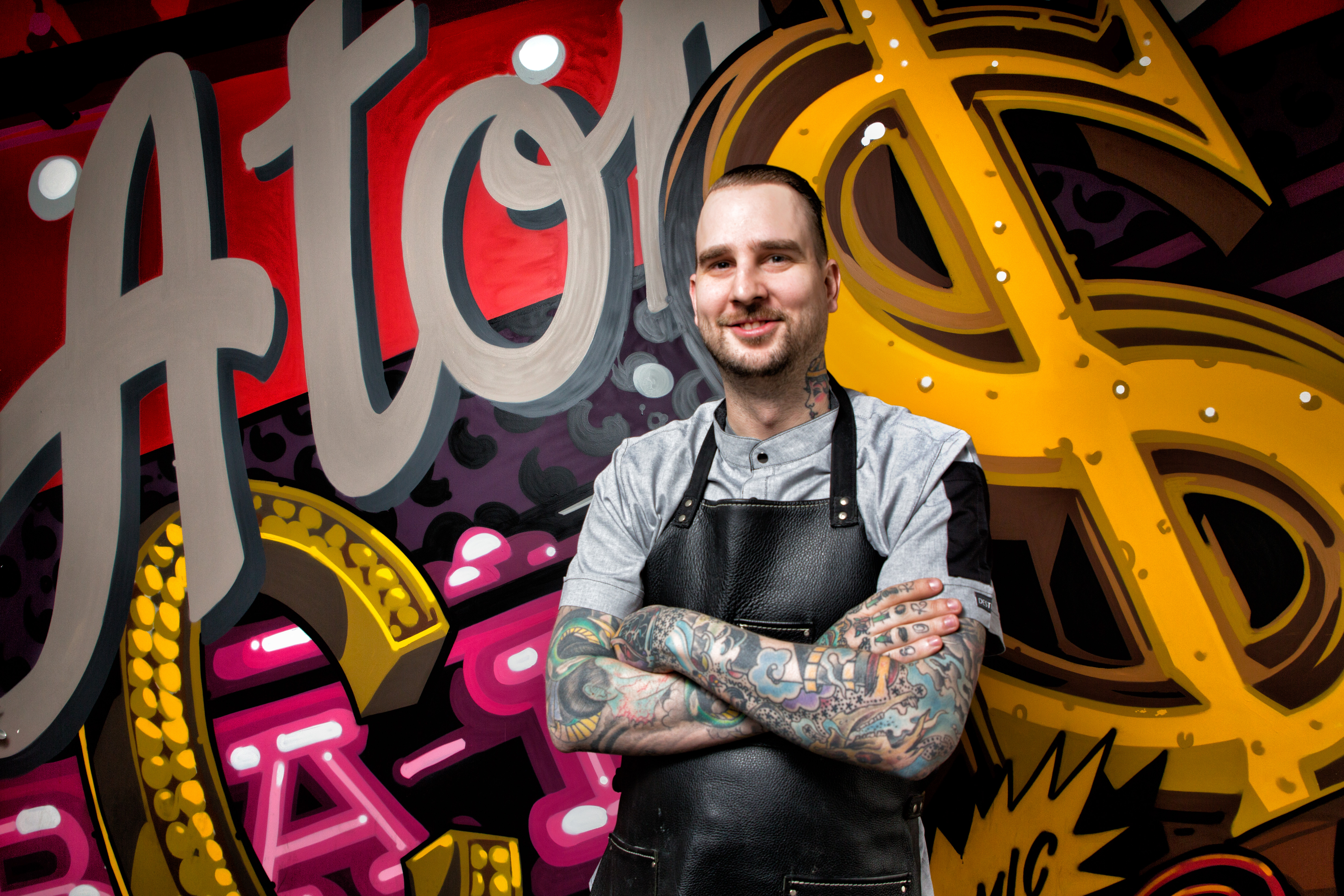 A chef with tattoos stands in front of a graffiti wall