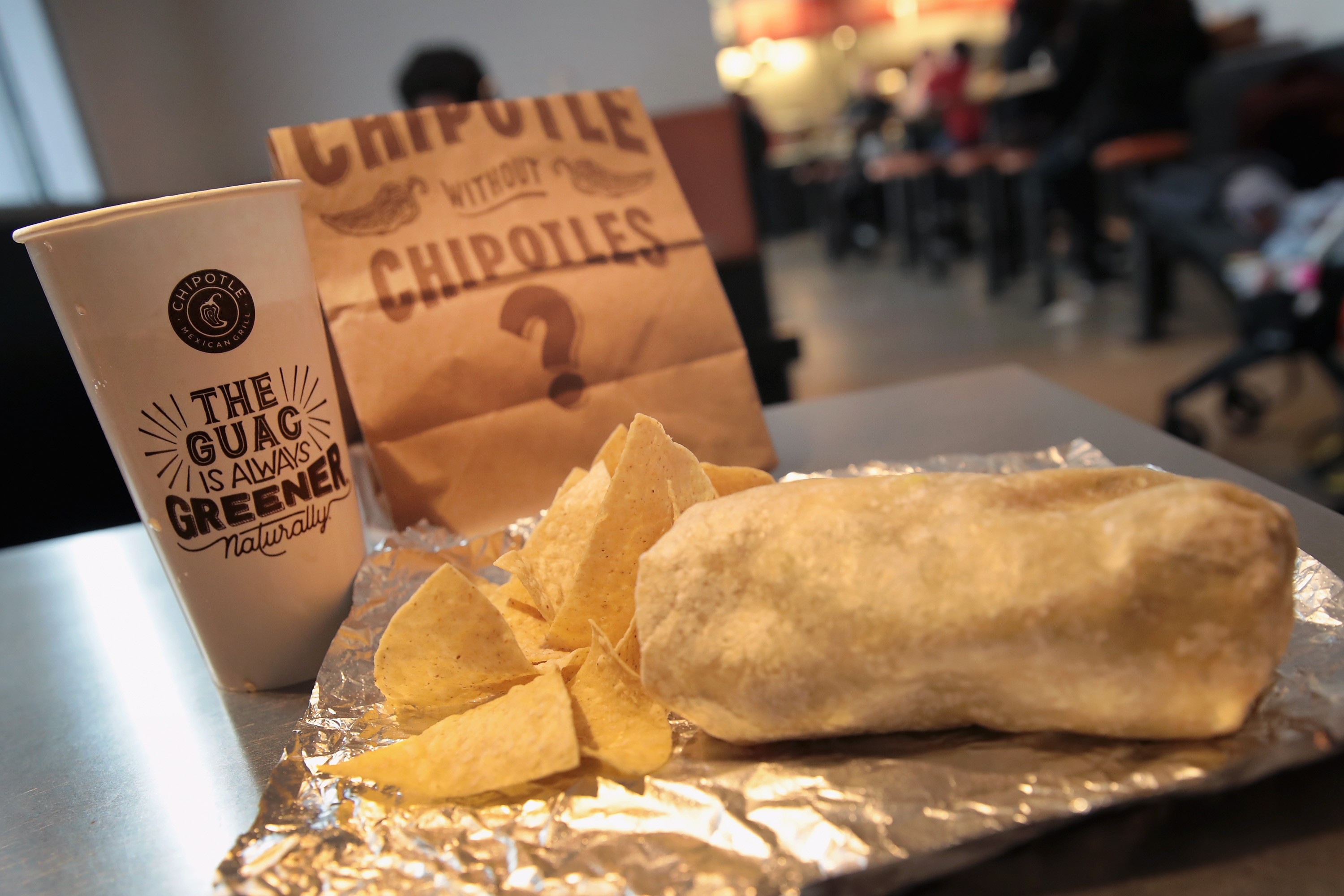 A photo of an unwrapped Chipotle burrito sitting on foil with chips beside a Chipotle drink cup and paper bag