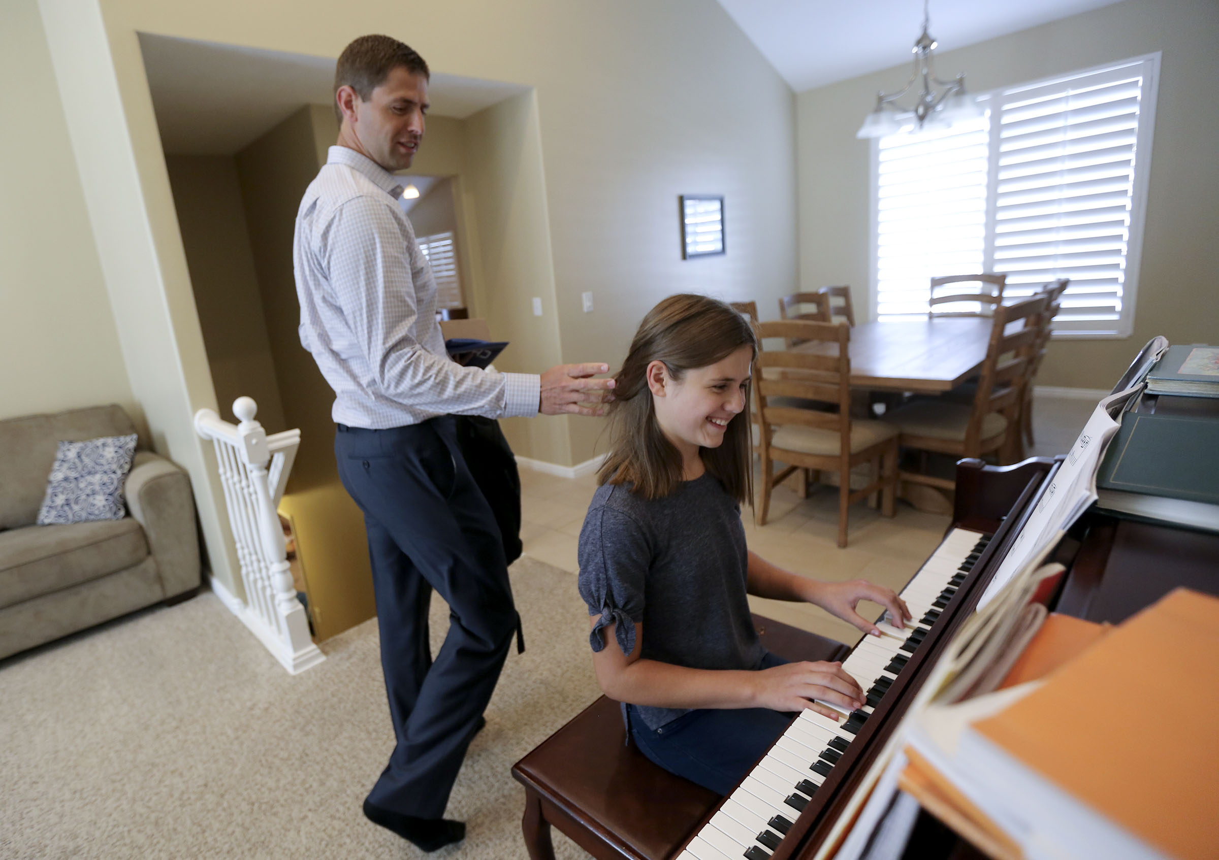 Matthew Grant pulls back his daughter Camilla's hair as she plays the piano at home in Midvale, Utah, on Monday, Sept. 9, 2019.