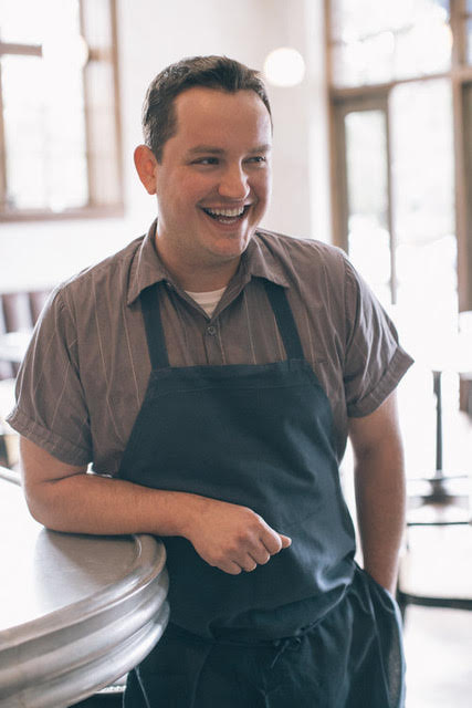 Jason stands at the end of the bar at St. Gen with one arm resting on the bar, wearing a short sleeved button down shirt and a blue apron. He's smiling with his face directed away from the camera.