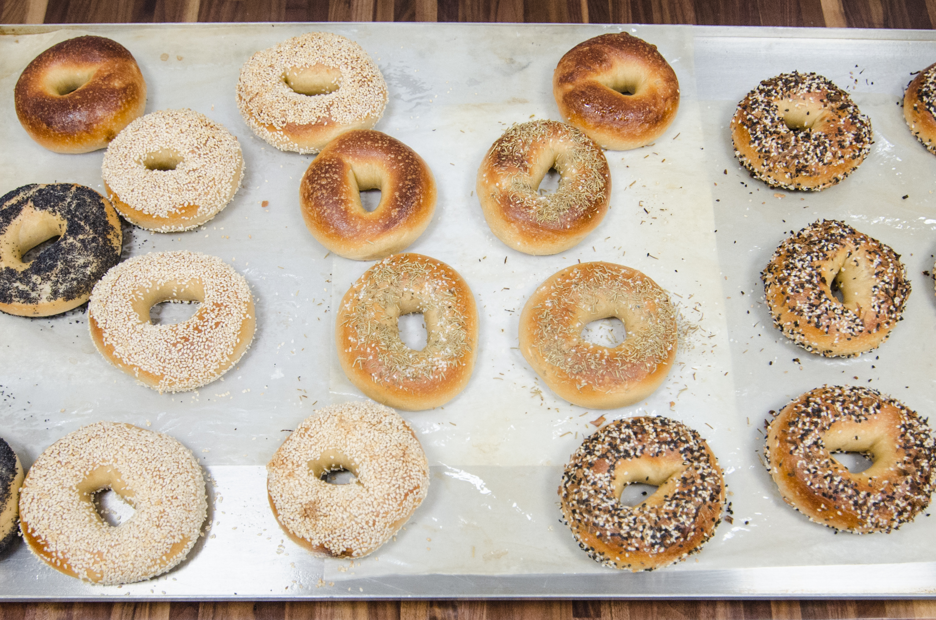Overhead view of a dozen or so bagels, including everything, poppy, sesame, and more