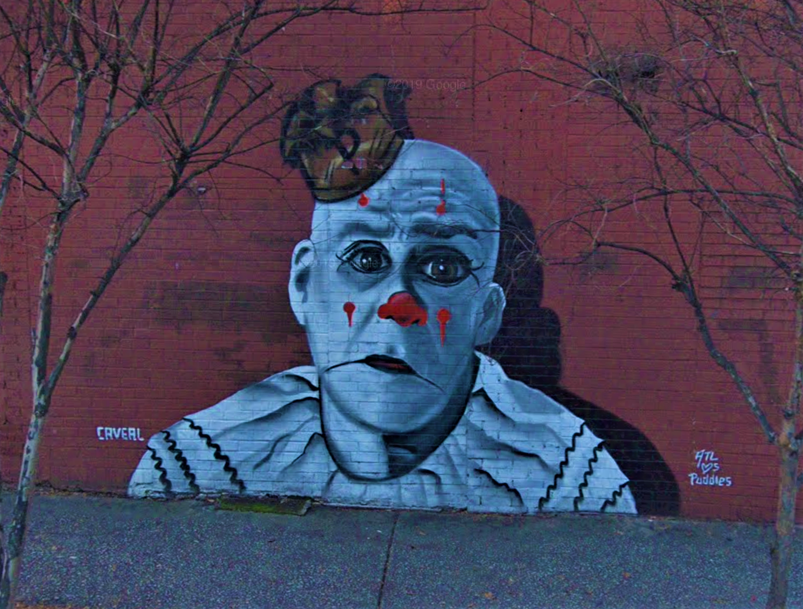 A mural of a sad clown painted on a red brick wall.