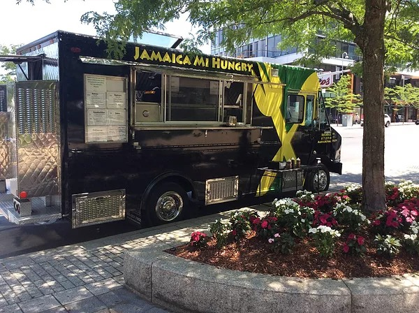 A black food truck painted with yellow and green parks on the street in front of a sidewalk planter with flowers and a tree