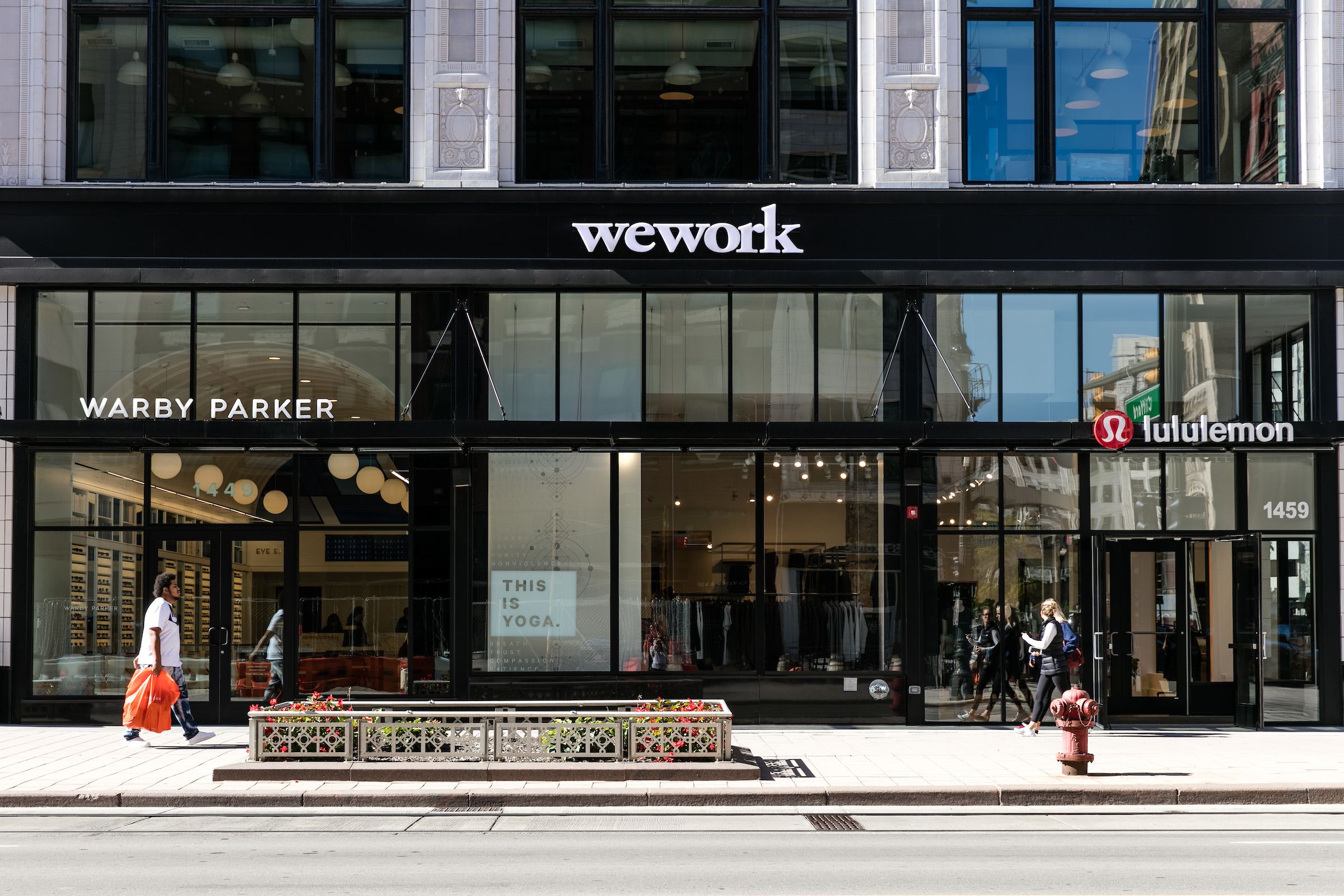 View from the street of the first two floors of a large building. There's three stores on the ground-floor: Warby Parker, WeWork, and Lululemon. The second floors have windows separated by white marble.