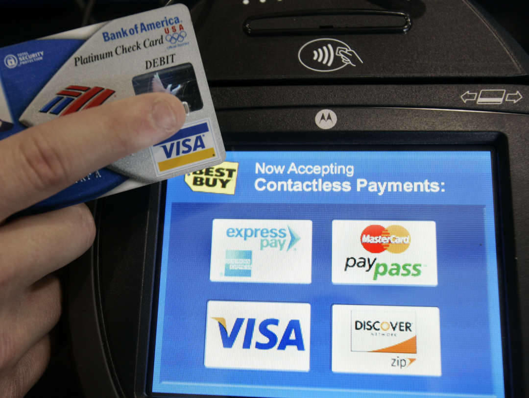 A Visa card holder holds up his card next to a credit card reader at Best Buy in Mountain View, Calif., Monday, Feb. 25, 2008.