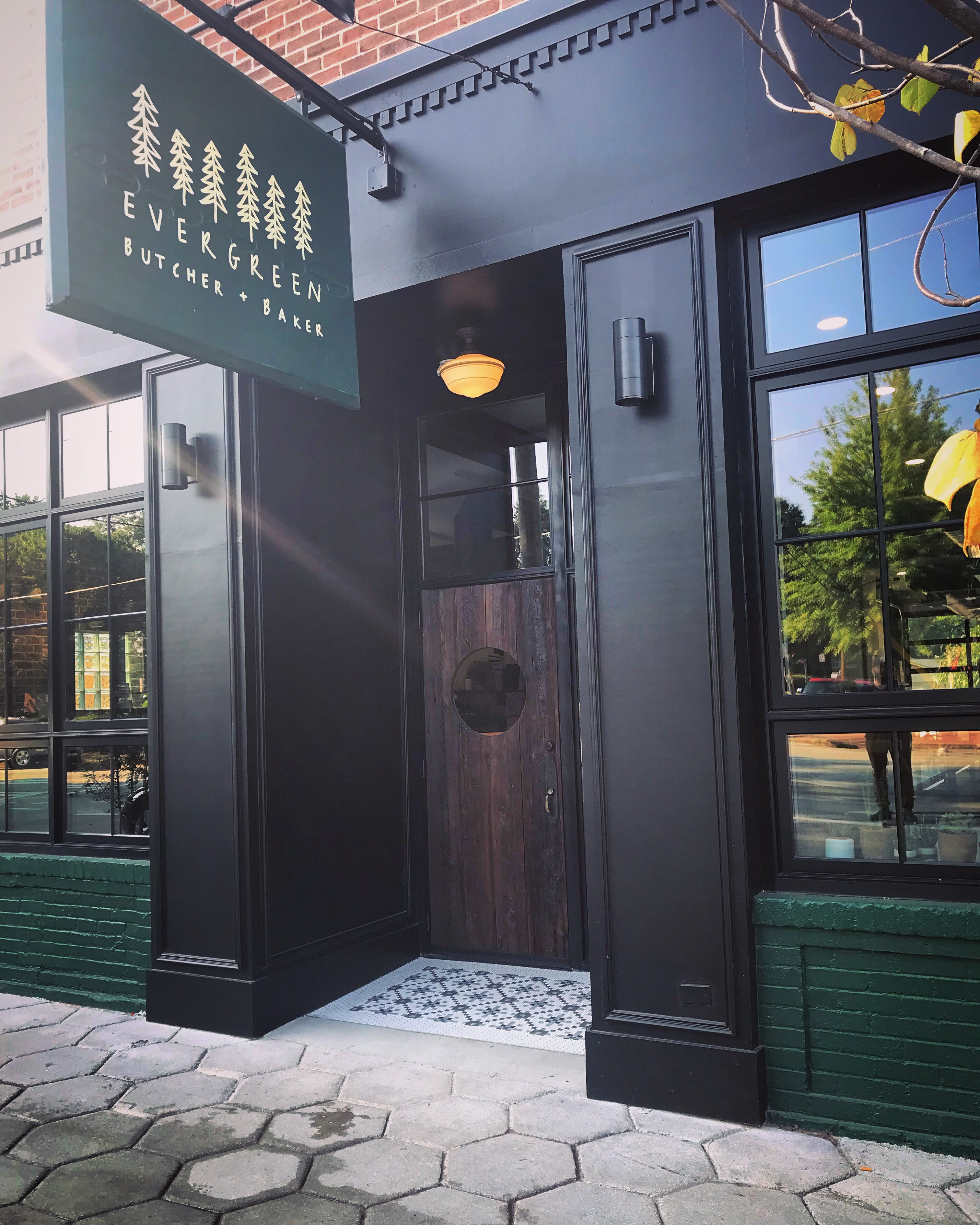 The green and black exterior entrance with sign hanging above the front door