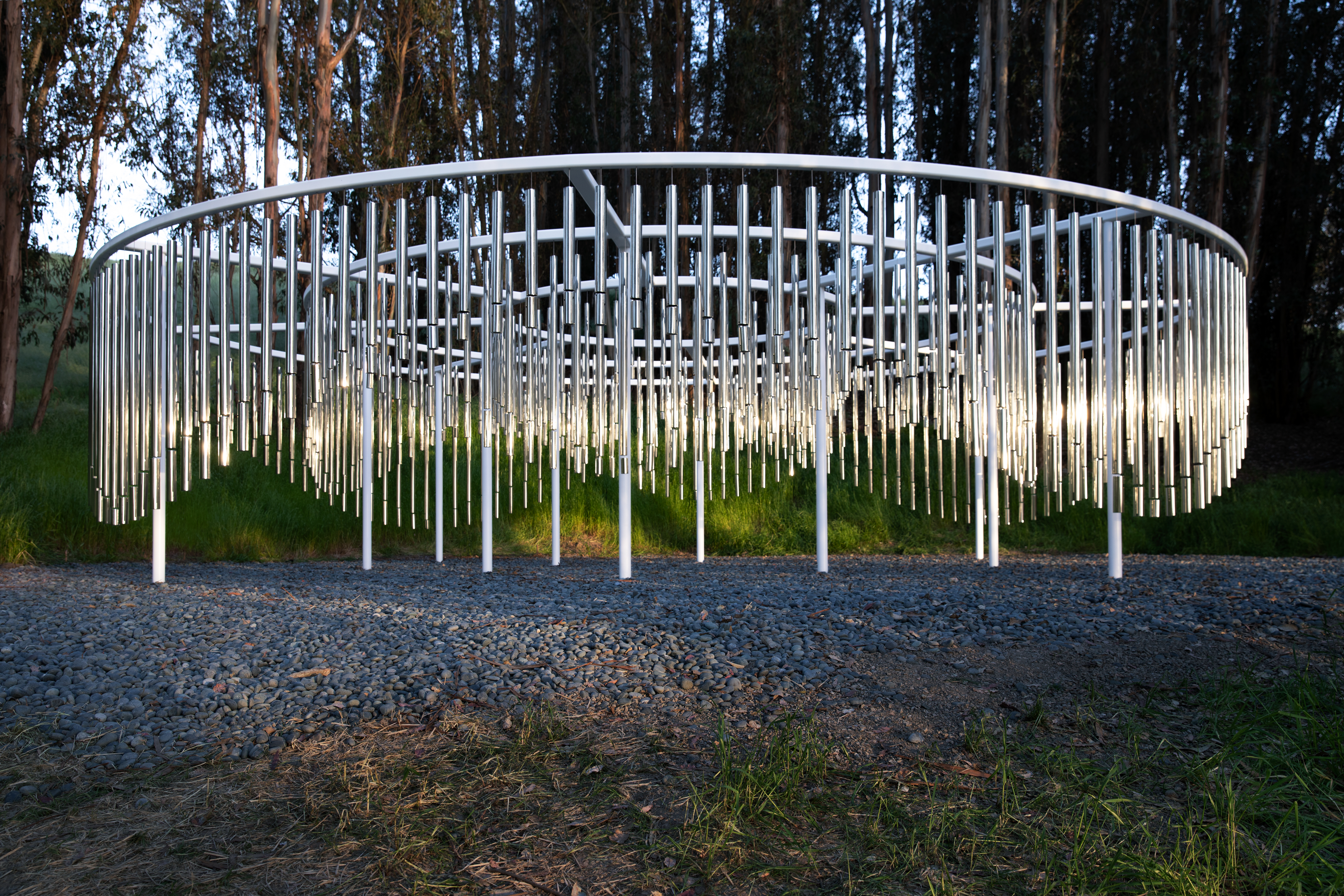 Large circular art work with gleaming steel rods dangling from it that look like massive wind chimes. The installation is set in a grove of trees.