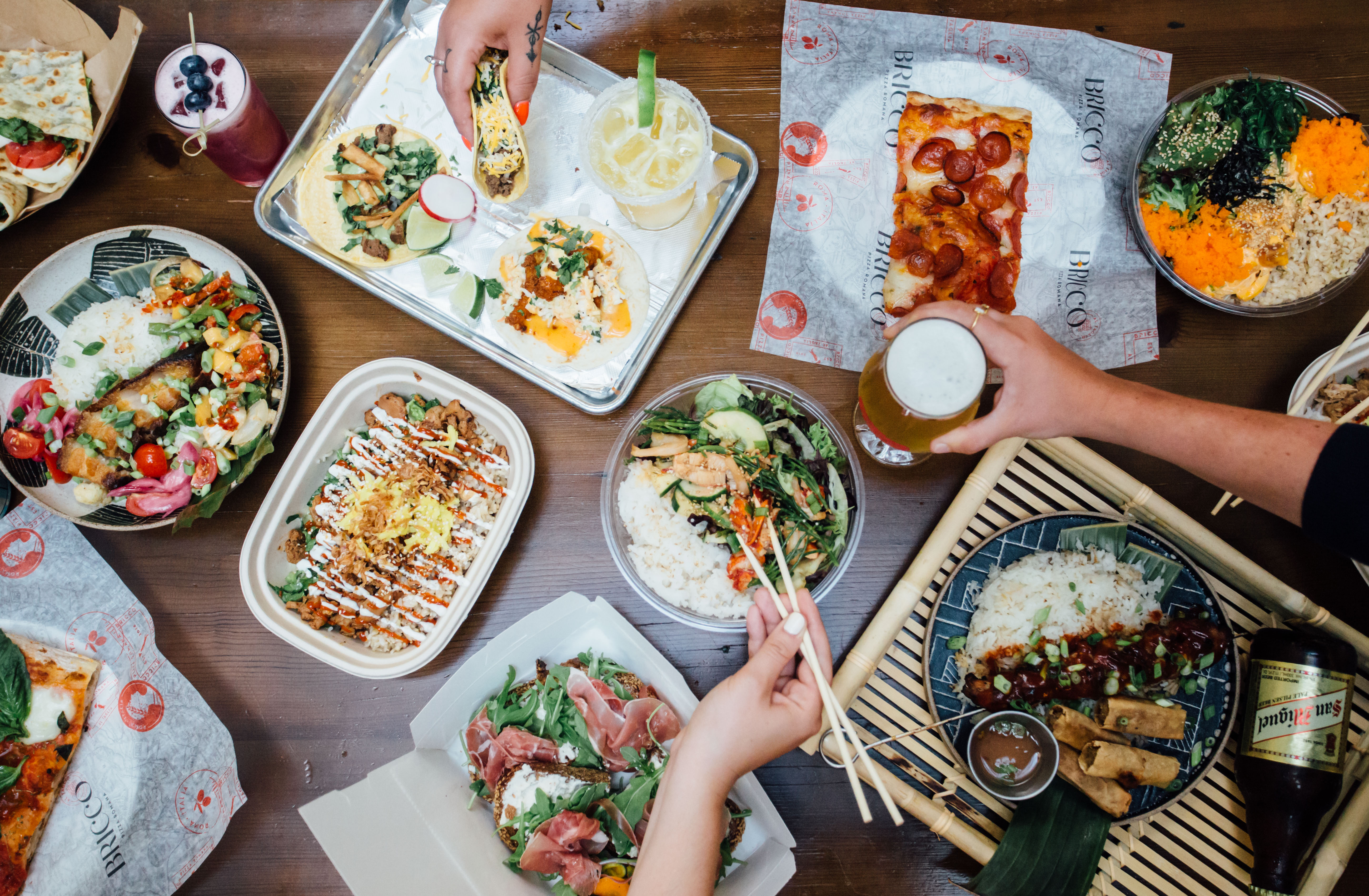 overhead shot of several plates of food including tacos and pizza