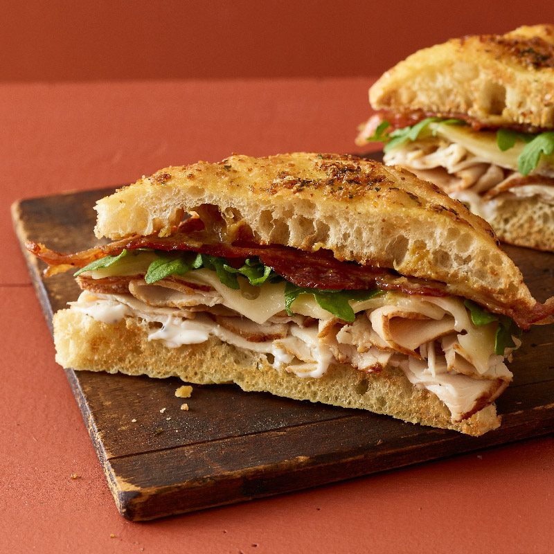 Two halves of a sandwich sit on a wooden board on an orange background. Turkey, bacon, greens, and cheese are sandwiched between pieces of focaccia bread.
