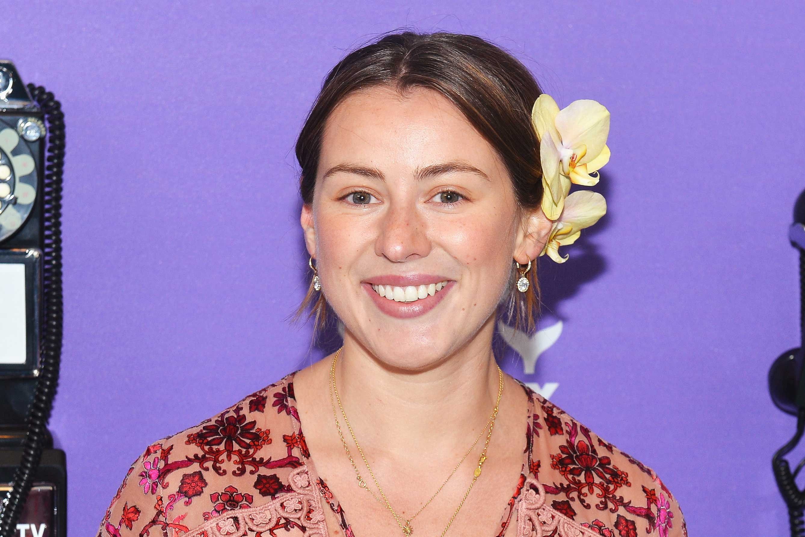A smiling woman with flowers in her hair stands in front of a purple wall.