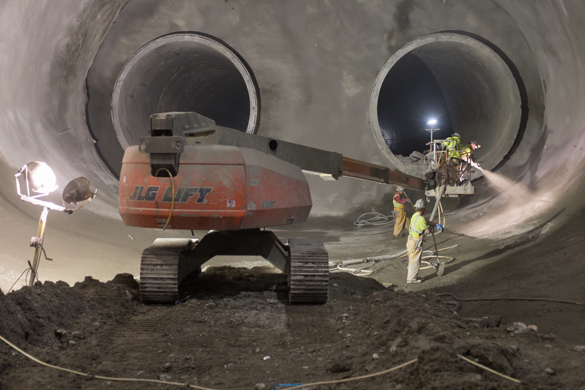 Underground view of two massive concrete subway tunnels with a construction crane.
