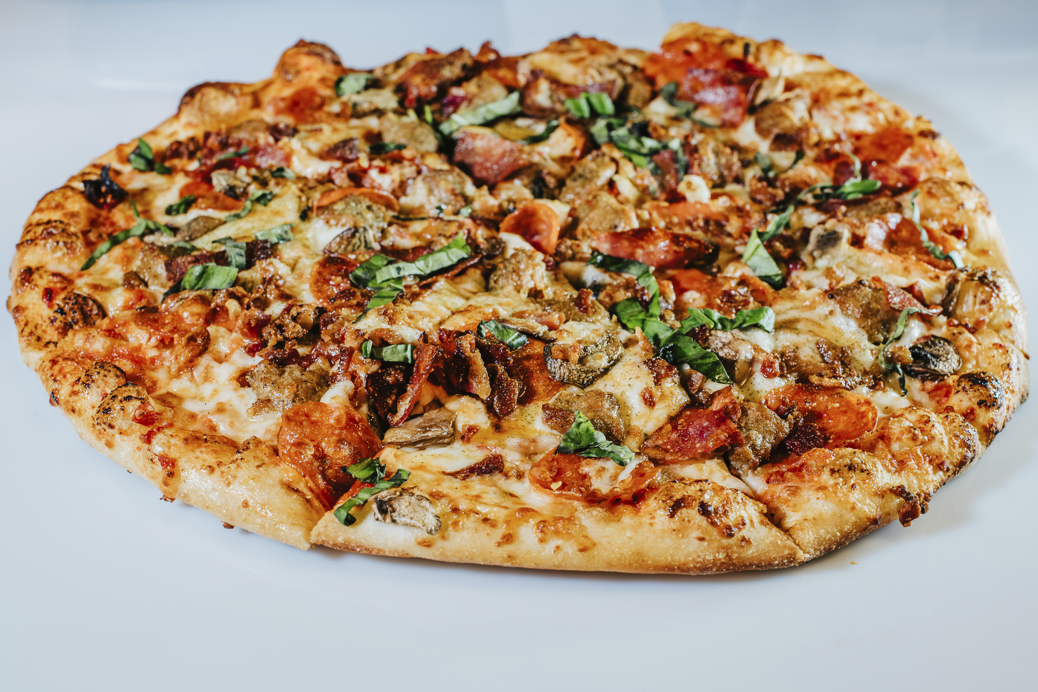 A closeup photo of the Magnificent 7 meatlover's pizza with pieces of pepperoni, sausage, bacon and basil visible on top of it