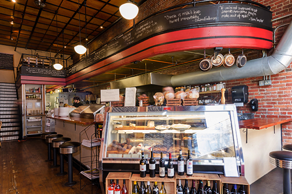 Interior of sandwich shop Delicatus, with a large glass display and a curved counter with menu items written at the top.