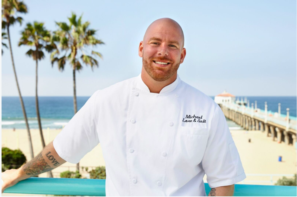Chef Michael Fiorelli stands in chef whites against the ocean backdrop.