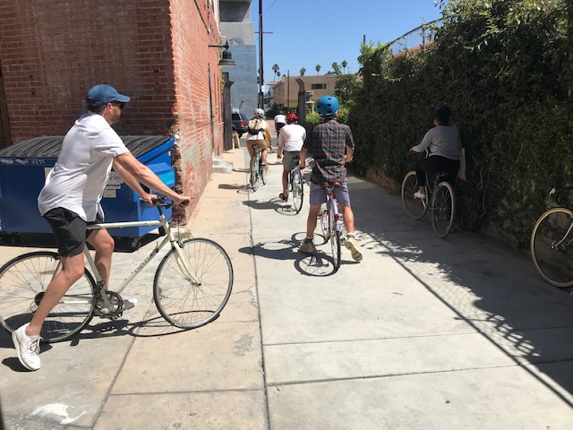 Five men and women mount bikes in an alley on a sunny day. There's a building with a brick facade, a blue dumpster, and a fence covered in ivy.