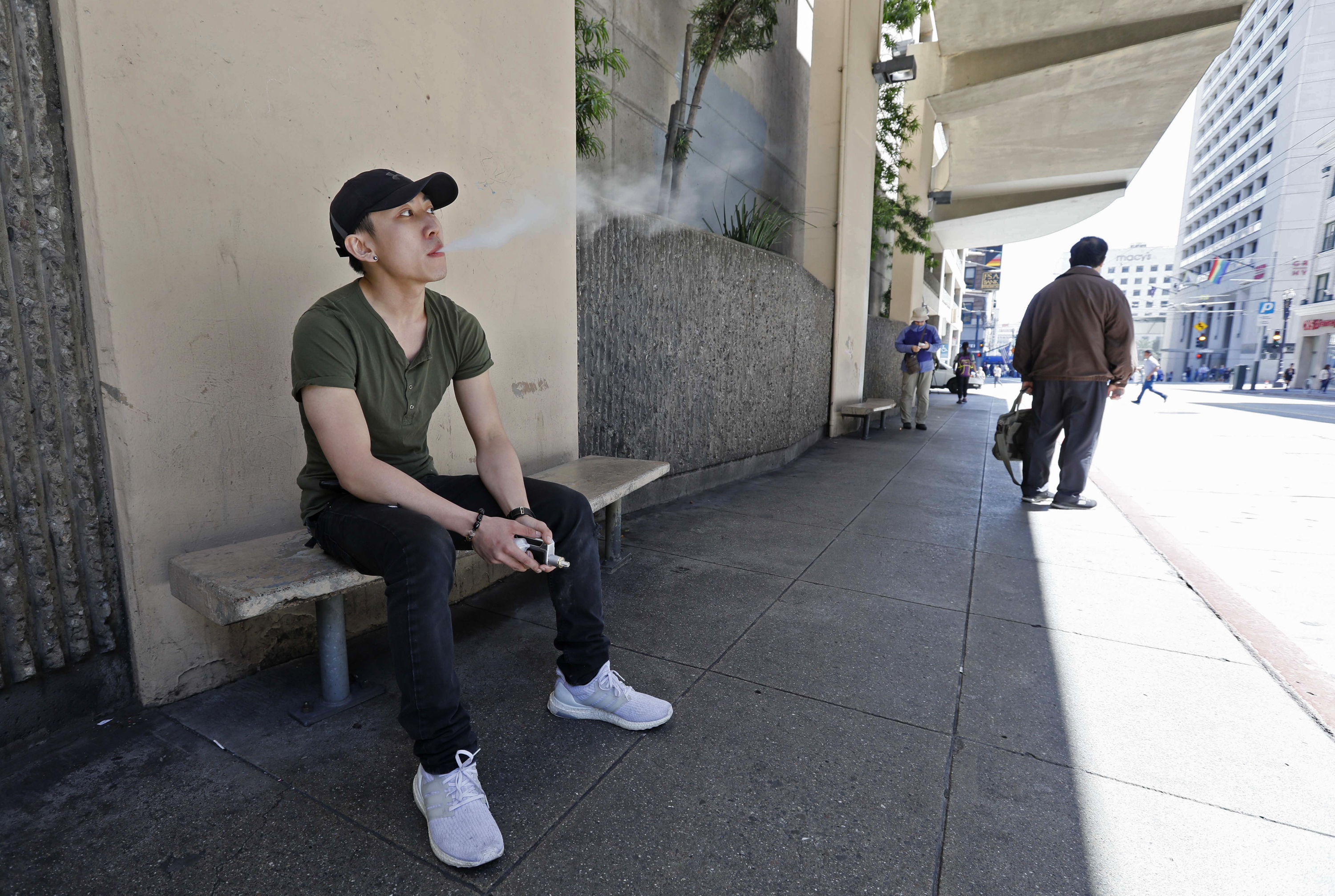 In this Monday, June 17, 2019, photo, Jacky Chan, 23, takes a vaping break from his job at a smoke shop in San Francisco. San Francisco supervisors are considering whether to move the city toward becoming the first in the United States to ban all sales of
