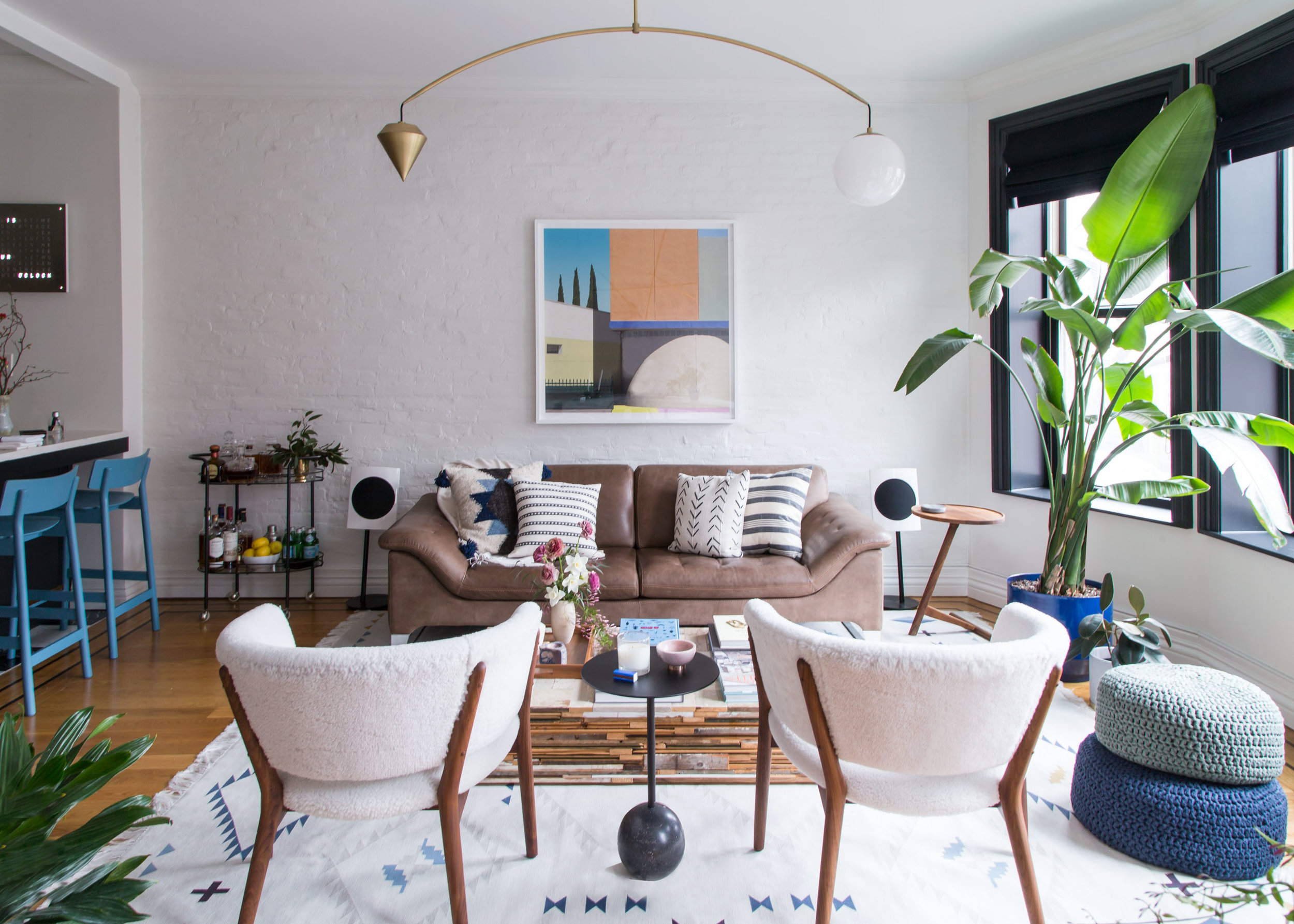 A brown two-seater sofa sits in the middle of a living room, which includes two white chairs, a black side table, a low coffee table with a vase filled with flowers, a large plant by the window, one framed geometric art piece on the wall, and a gold penda