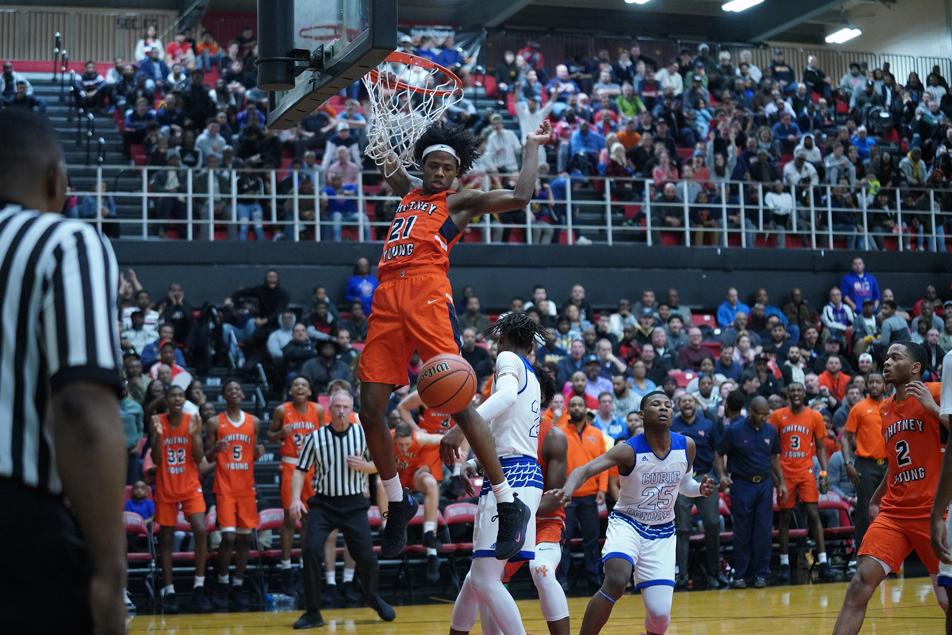 Young's DJ Steward (21) gets a fast break for a dunk against Curie.