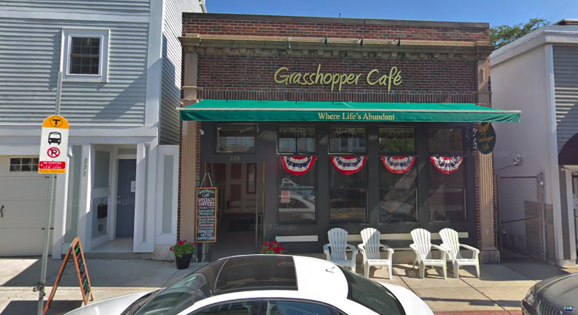 A brick restaurant with a green awning features red, white, and blue bunting in each vertical windows