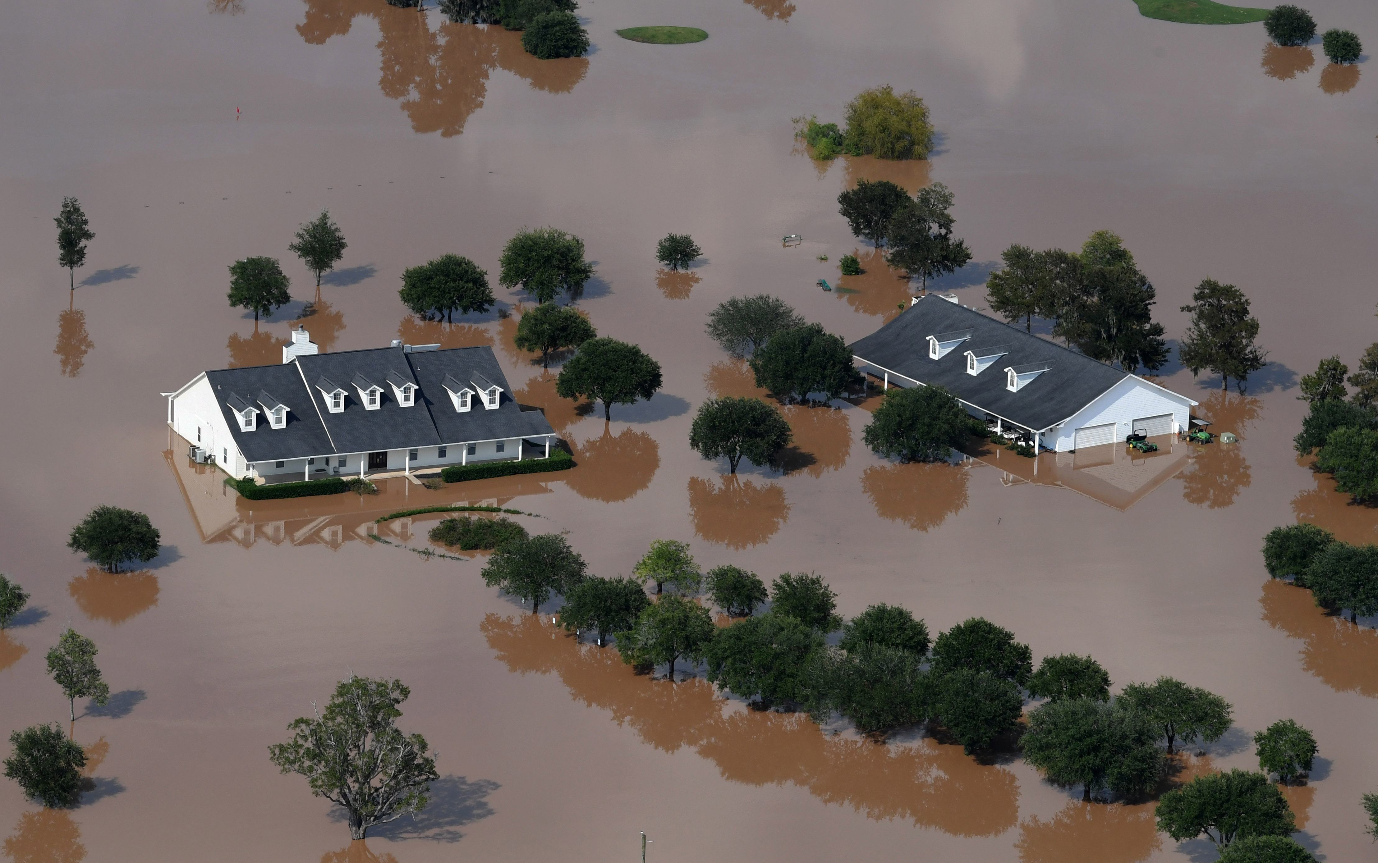 Rising brown floodwaters engulf a pair of white, two-story single-family homes