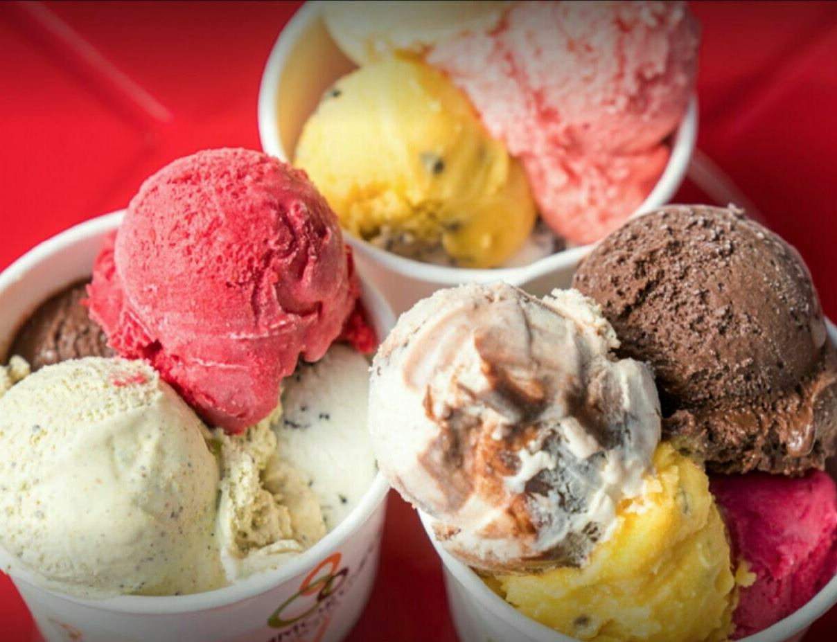 Three large cups of colorful gelato sit side by side.