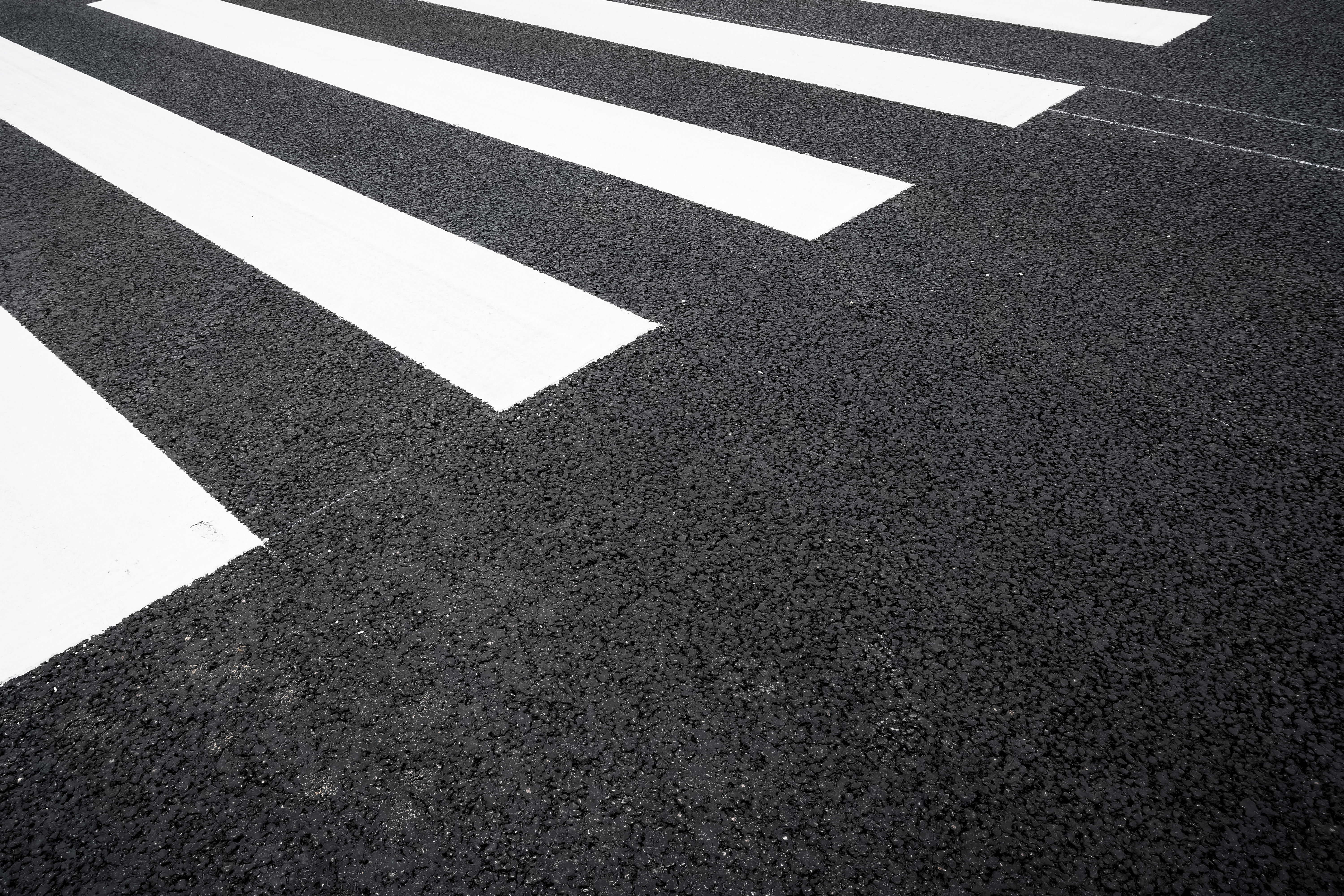 A high-visibility crosswalk in the middle of a black-asphalt road.