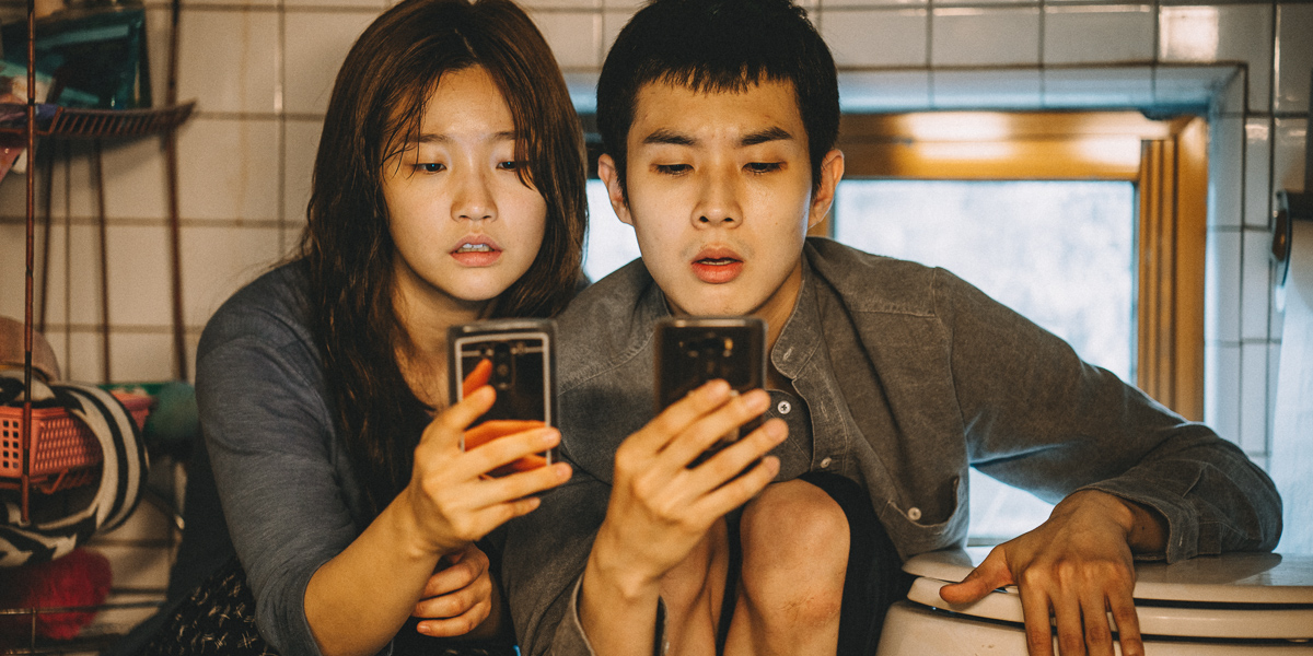 "Park So-dam and Choi Woo-sik sit close to one another on the floor of a bathroom while each stares at their phone in the movie ""Parasite."""