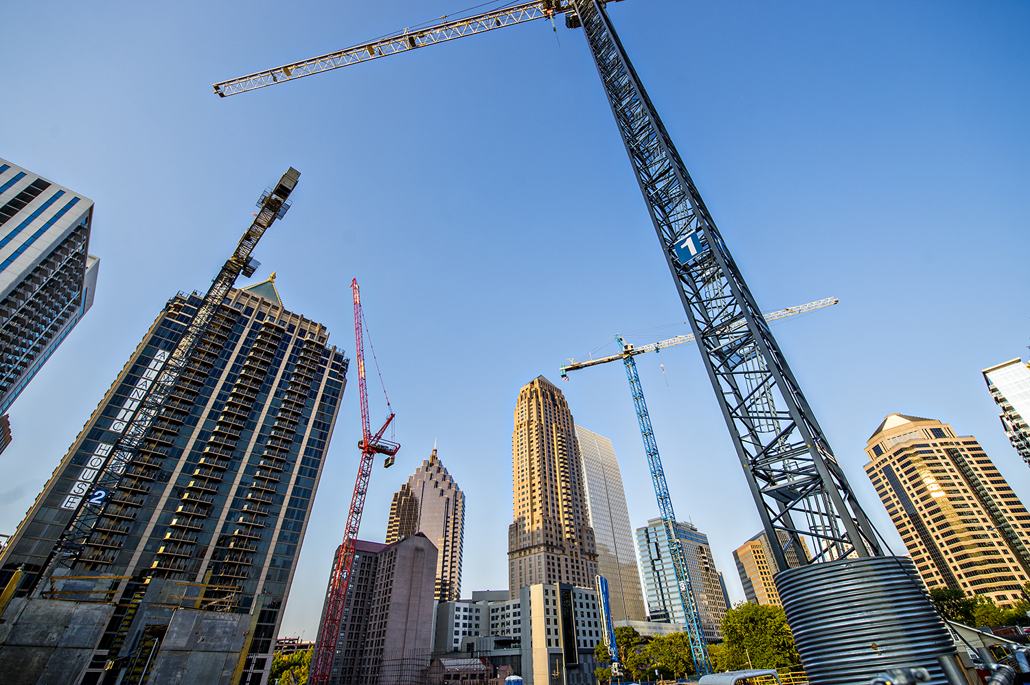 A blue sky with several construction cranes set against it and exiting tall buildings.