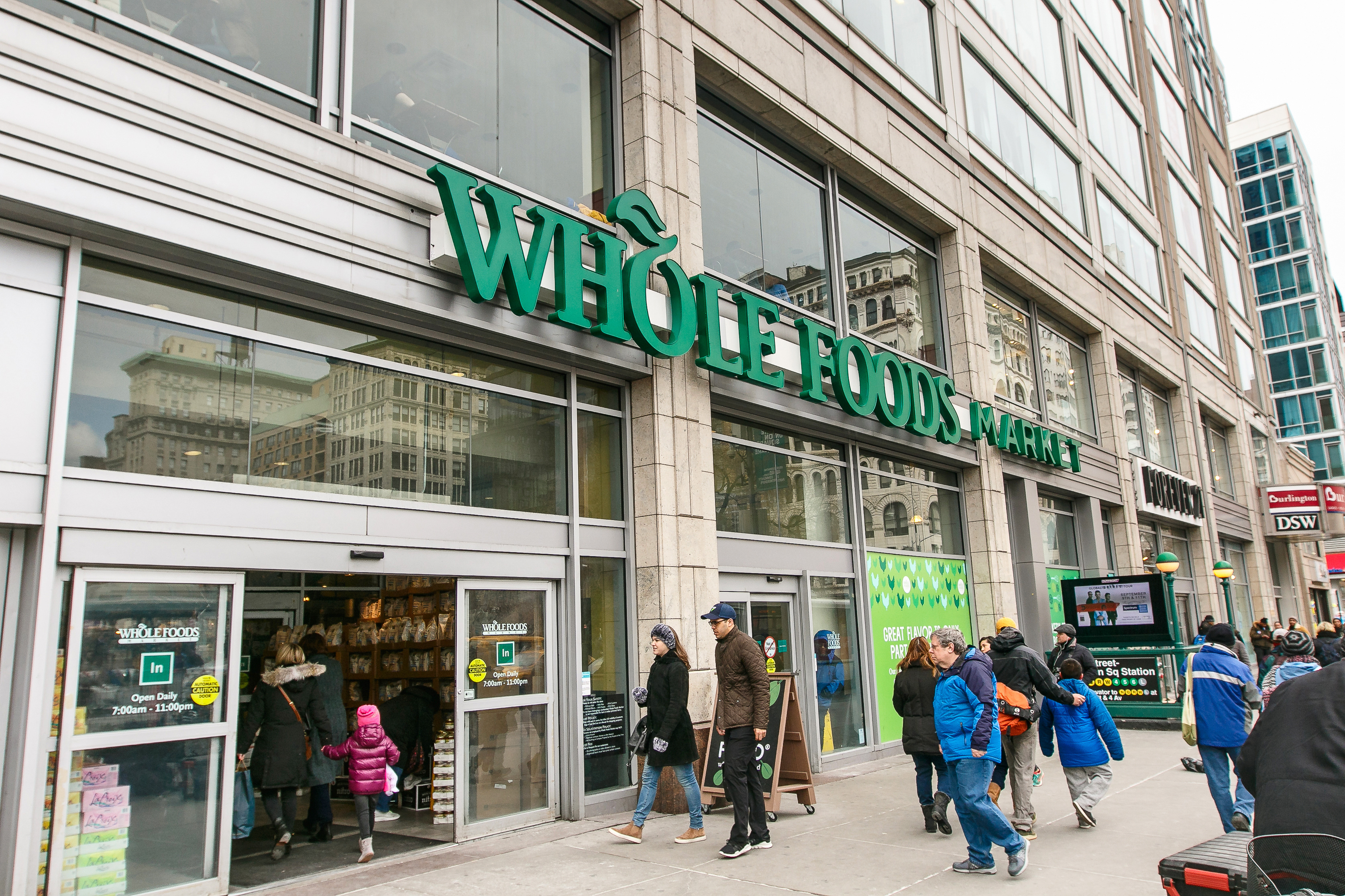 Store front of a Whole Foods Market in New York, shown with people walking in and out of the store.