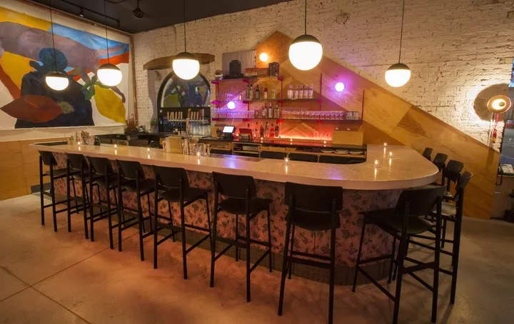 The bar area features limewashed brick paneling, colorful artwork, hanging lights, and black barstools.