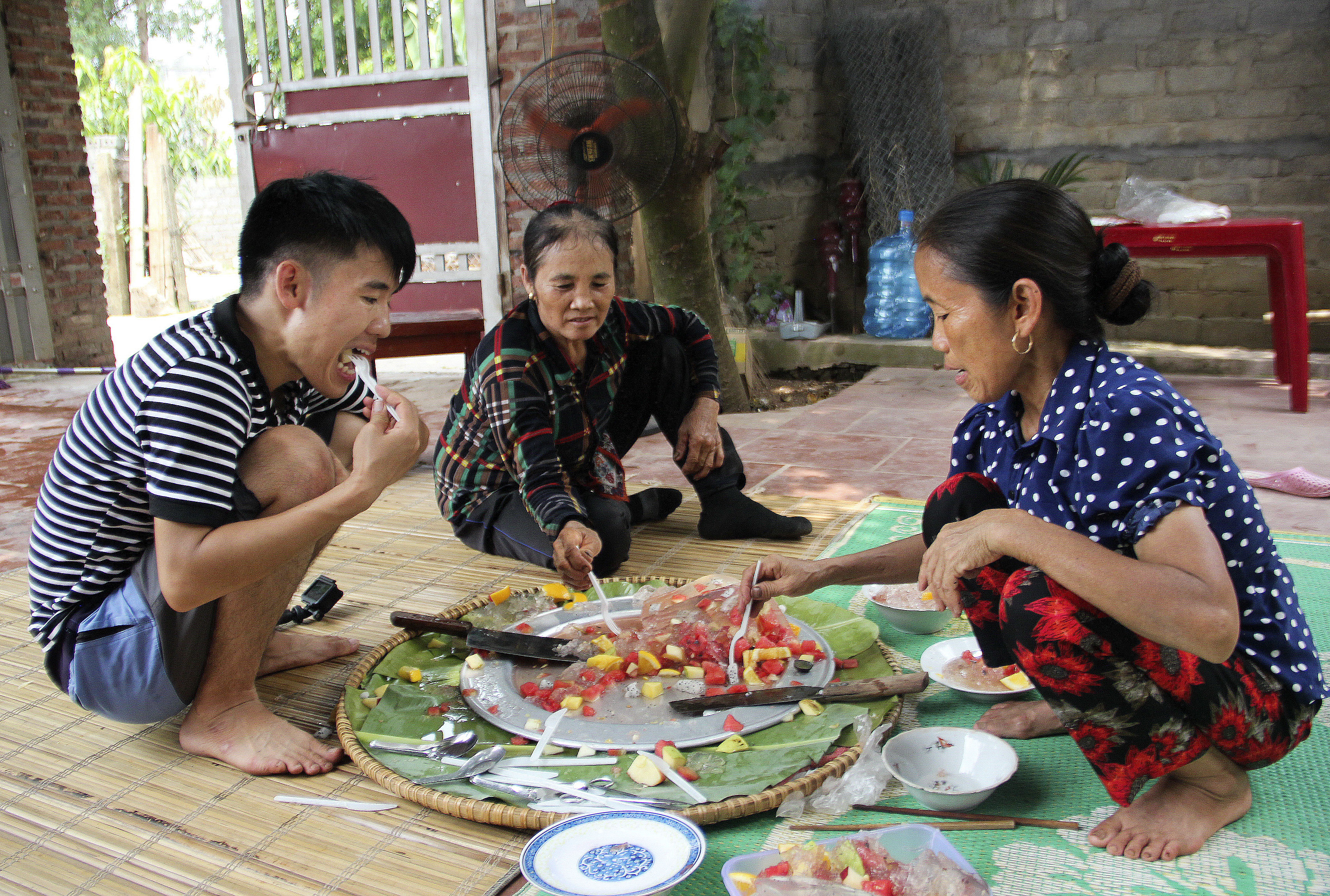 Nguyen Thi Tan, 51, right, and her son, Nguyen Van Hung, 27, left, grab a bite to eat along with a friend from their village, following the taping of an episode of her popular YouTube channel in Xuan Huong, Vietnam, on Friday, July 19, 2019.