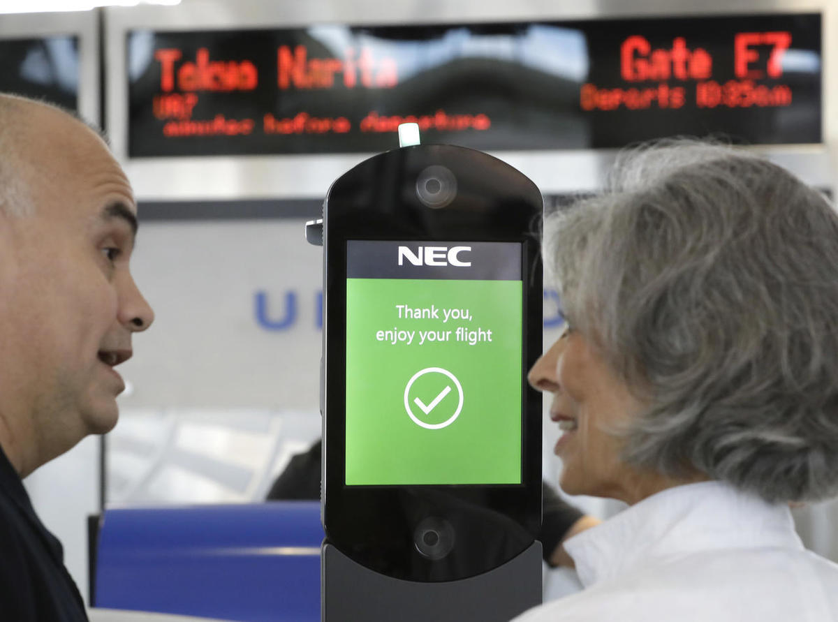 U.S. Customs and Border Protection officer Sanan Jackson, left, helps a passenger navigate one of the new facial recognition kiosks at a United Airlines gate before boarding a flight to Tokyo, Wednesday, July 12, 2017, at George Bush Intercontinental Airp