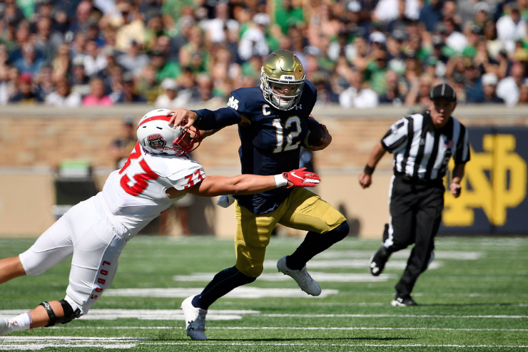 Notre Dame quarterback Ian Book eludes the tackle of Alex Hart on Saturday in South Bend, Ind.