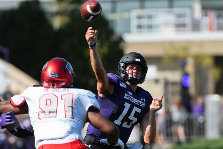 Northwestern quarterback Hunter Johnson passes over UNLV defensive lineman Nate Neal on Saturday in Evanston.