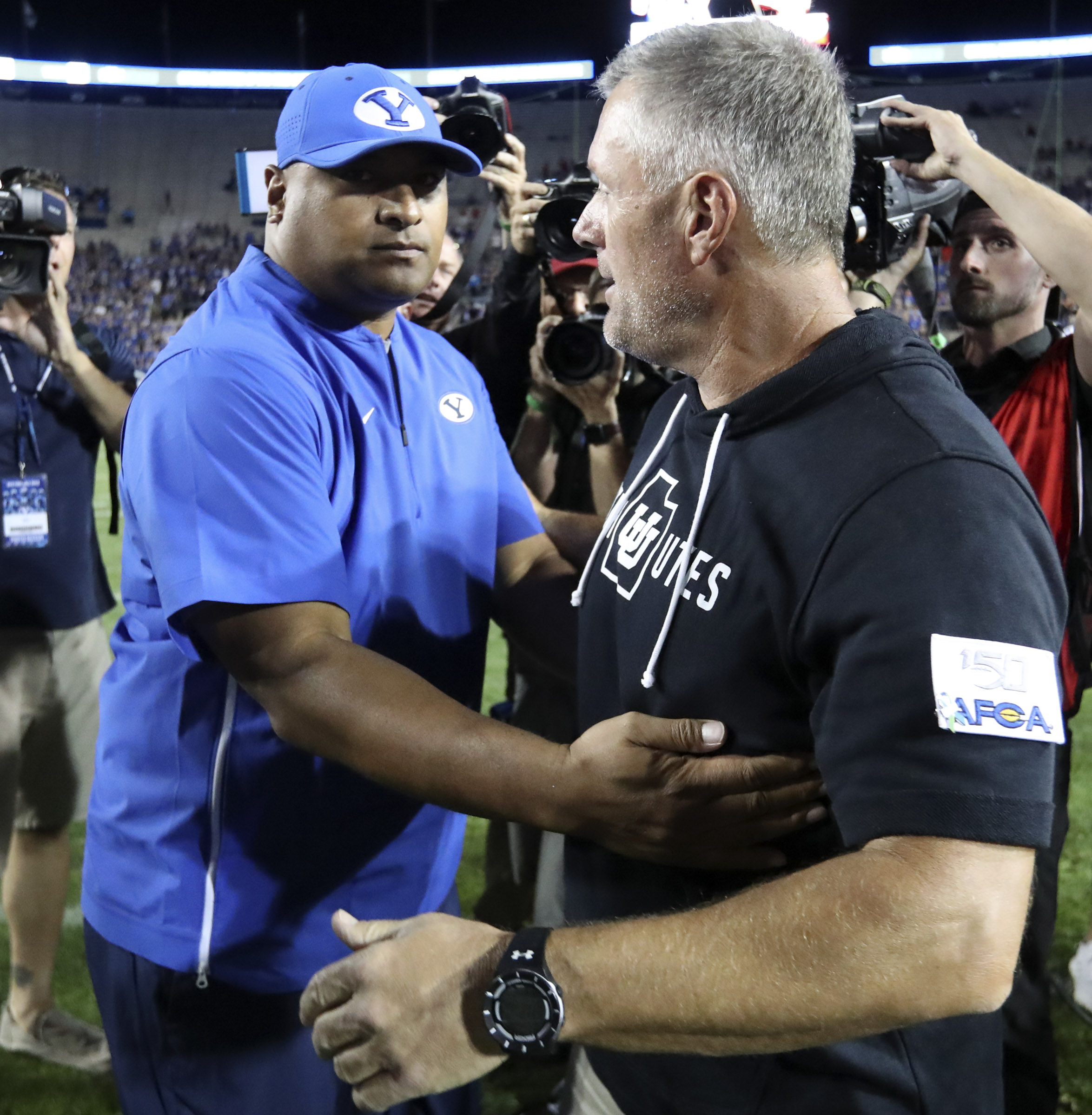 BYU head coach Kalani Sitake and Utah head coach Kyle Whittingham congratulate each other after Utah defeated BYU 30-12 at LaVell Edwards Stadium in Provo on Friday, Aug. 30, 2019.