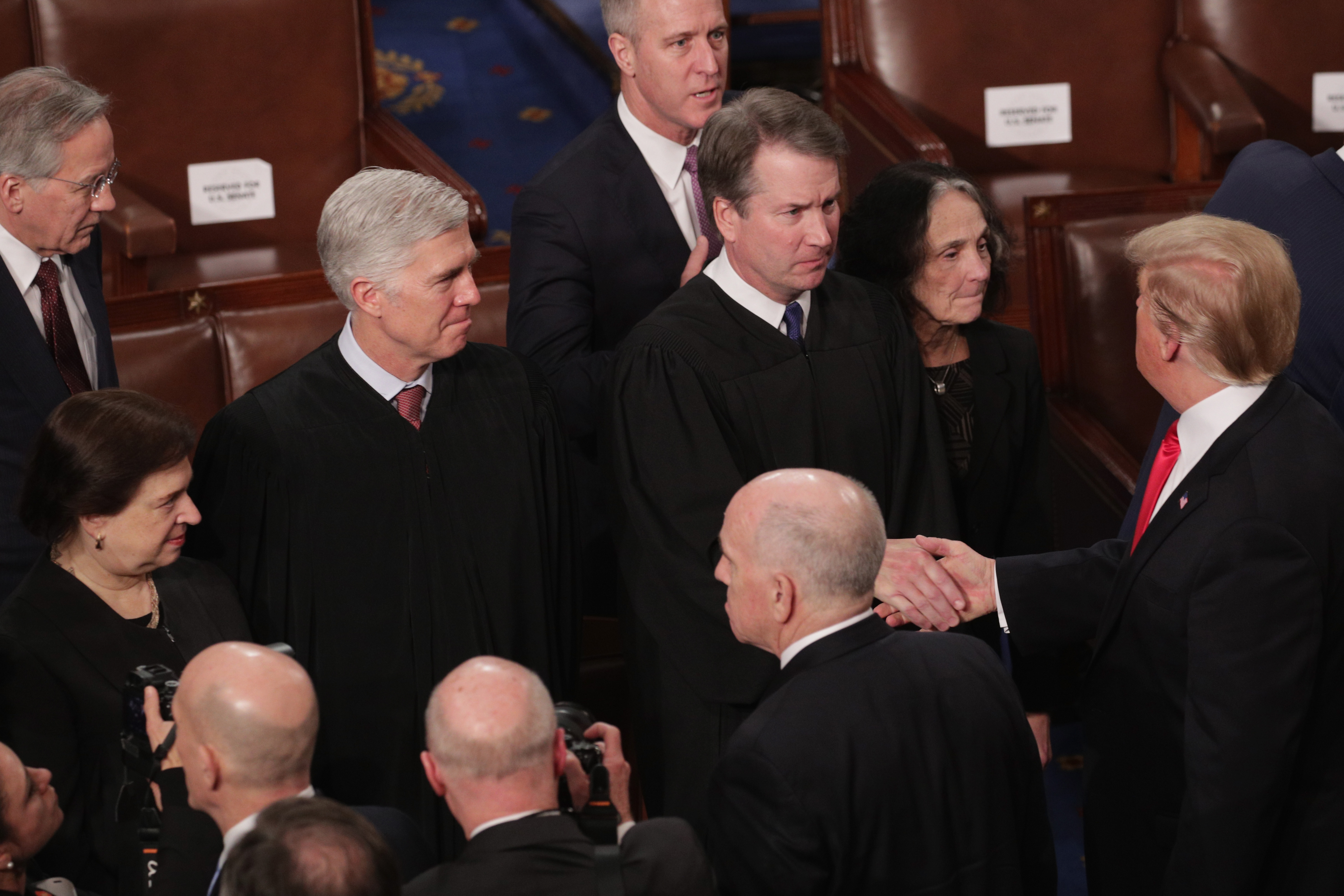 Supreme Court Justice Brett Kavanaugh shakes hands with President Donald Trump after the State of the Union address, as other justices look on, at the U.S. Capitol Building on February 5, 2019 in Washington, DC.