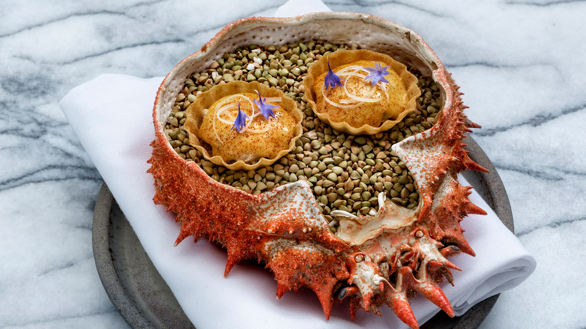 Spider crab tartlets served in a crab shell filled with sea gravel at Michelin-starred London restaurant The Clove Club