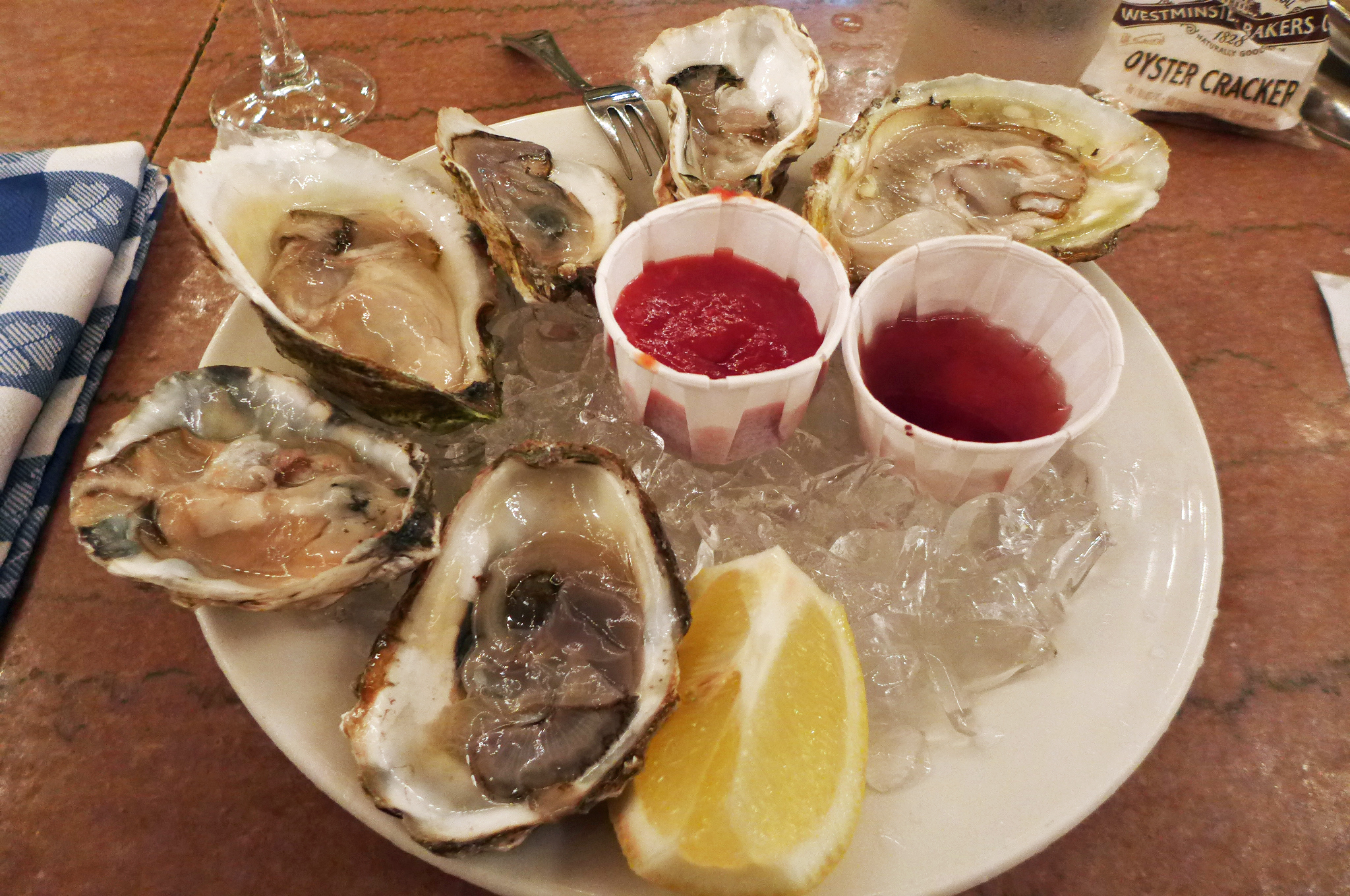 Six oysters of different shapes and sizes, on a plate lined with ice, served with a lemon wedge...