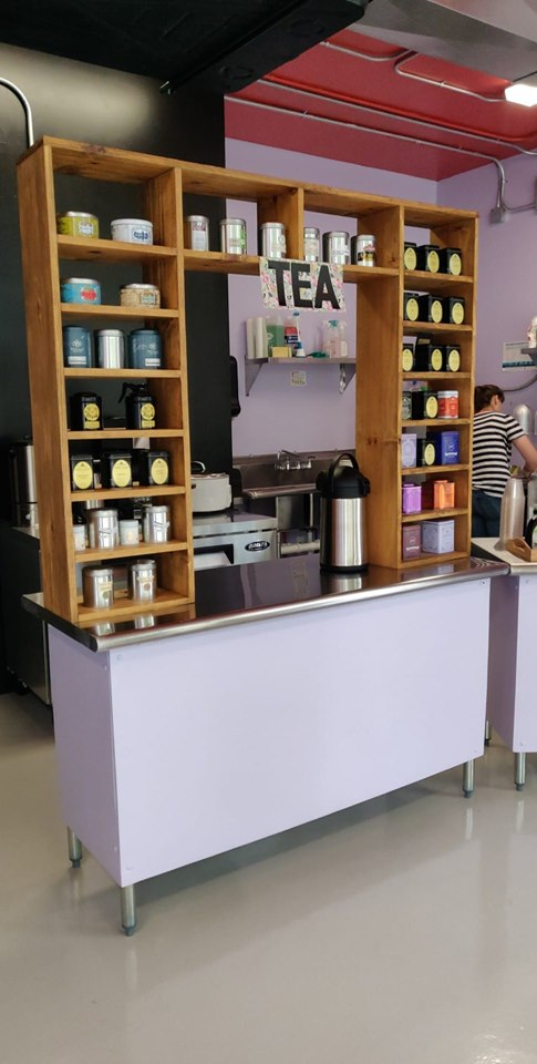 """A purple table with a metal counter and a wooden shelf on top with a sign that reads """"tea"""" and cubbies filled with tins of loose tea."""