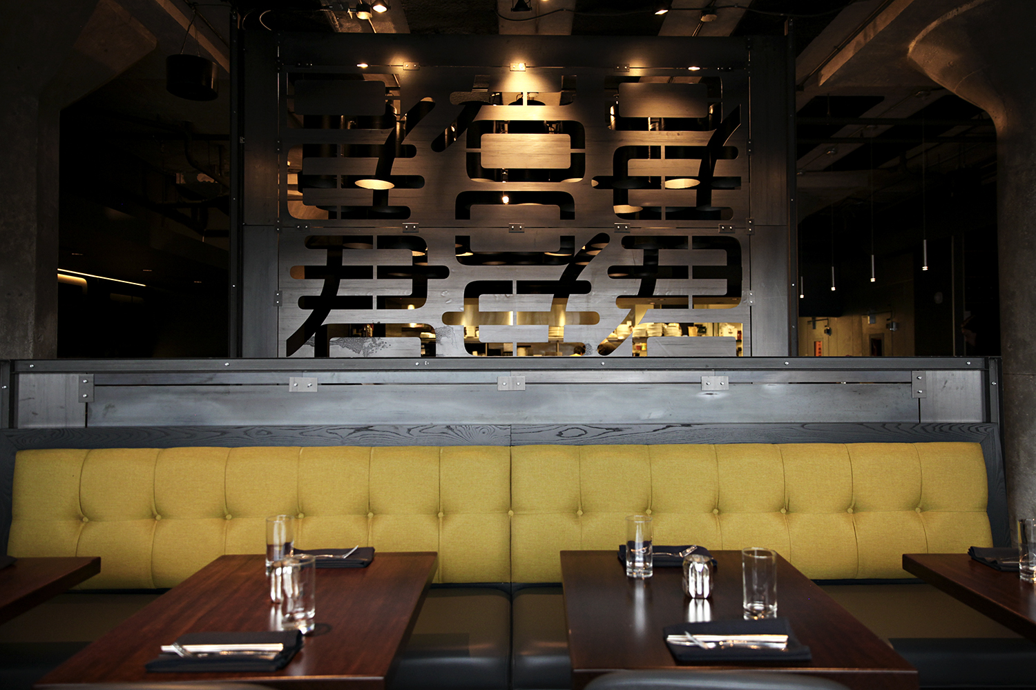 A plexiglass piece with Chinese characters hangs behind a gold-backed booth and a set table.