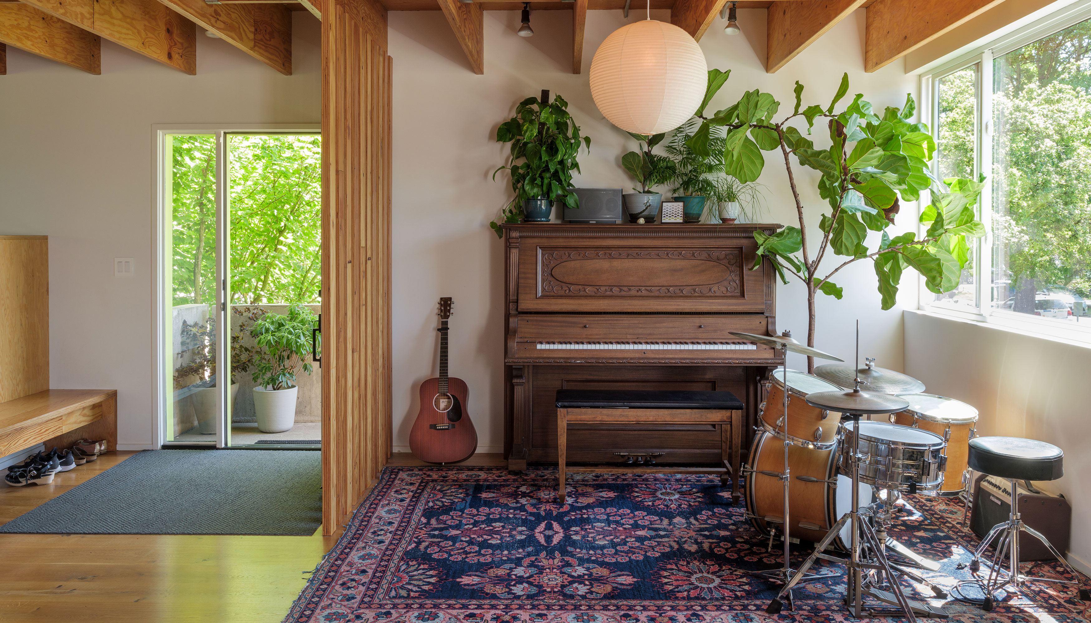 A living area with a wooden upright piano, guitar, patterned area rug, drum set, and light fixture. There are wooden beams on the ceiling and a wood room divider.