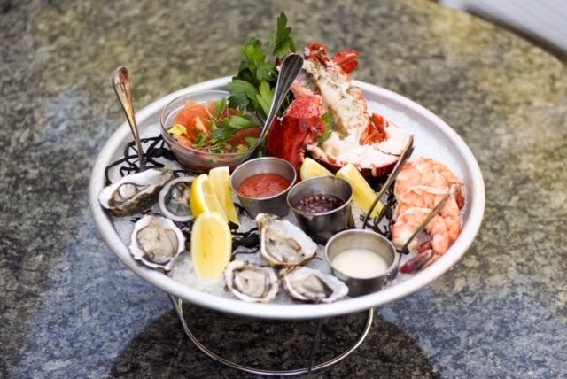 A full platter of seafood sitting on an iced tray.