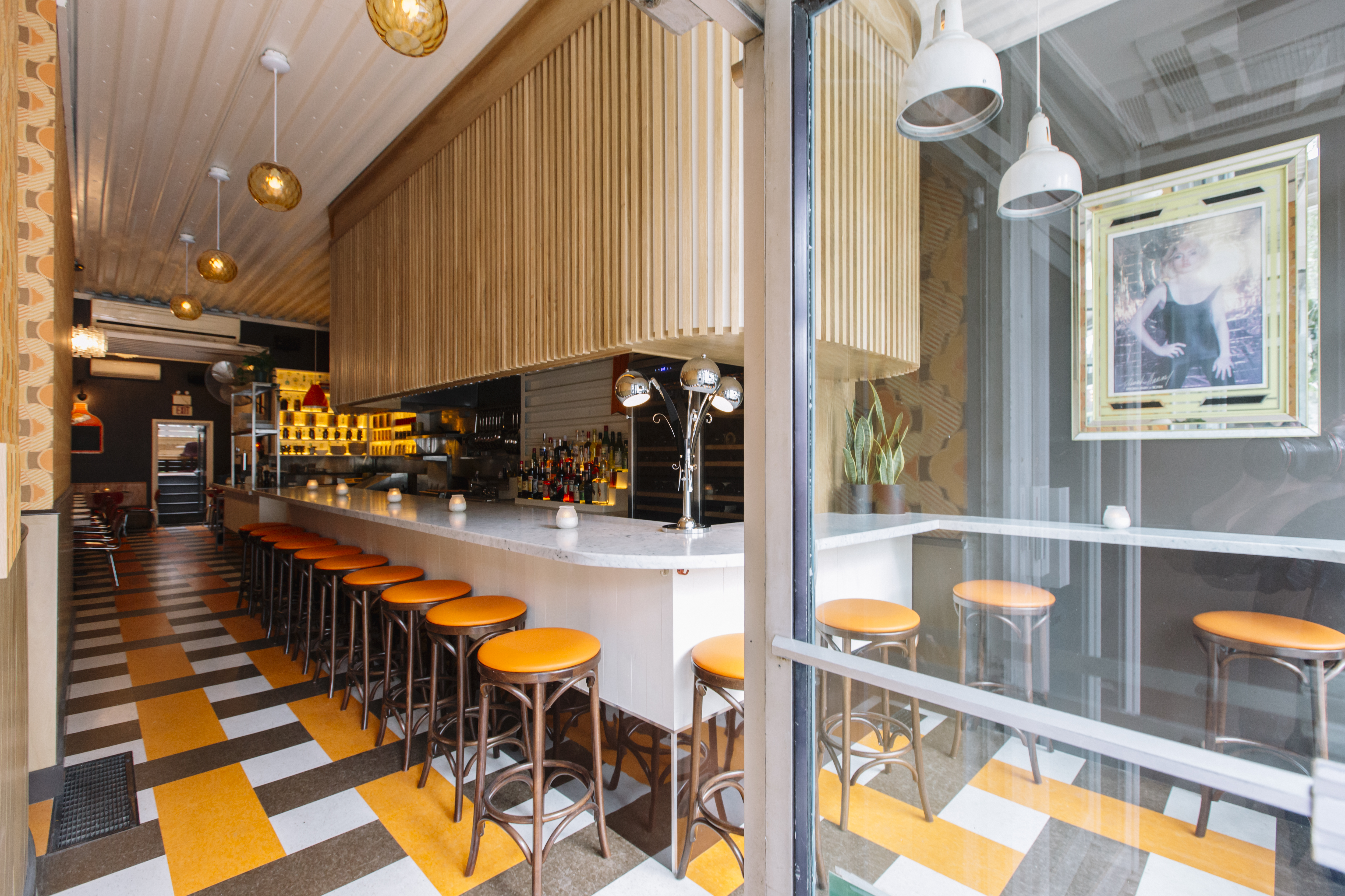 A view into a restaurant space from an open front door include orange, white, and black linoleum floors and a long bar with orange-cushioned stools
